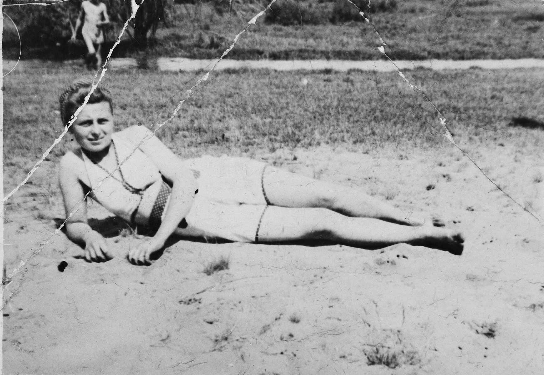 """Rachel Kolin relaxes on a beach in Olkusz.  The donor, Hela, had this photo with her in the Markstadt labor camp and gave it to her future husband, Szulim, before the two became separated.  Hela inscribed the photo with the message, """"I don't have a picture of me, so I give you a picture of my sister, one that I will never forget."""""""