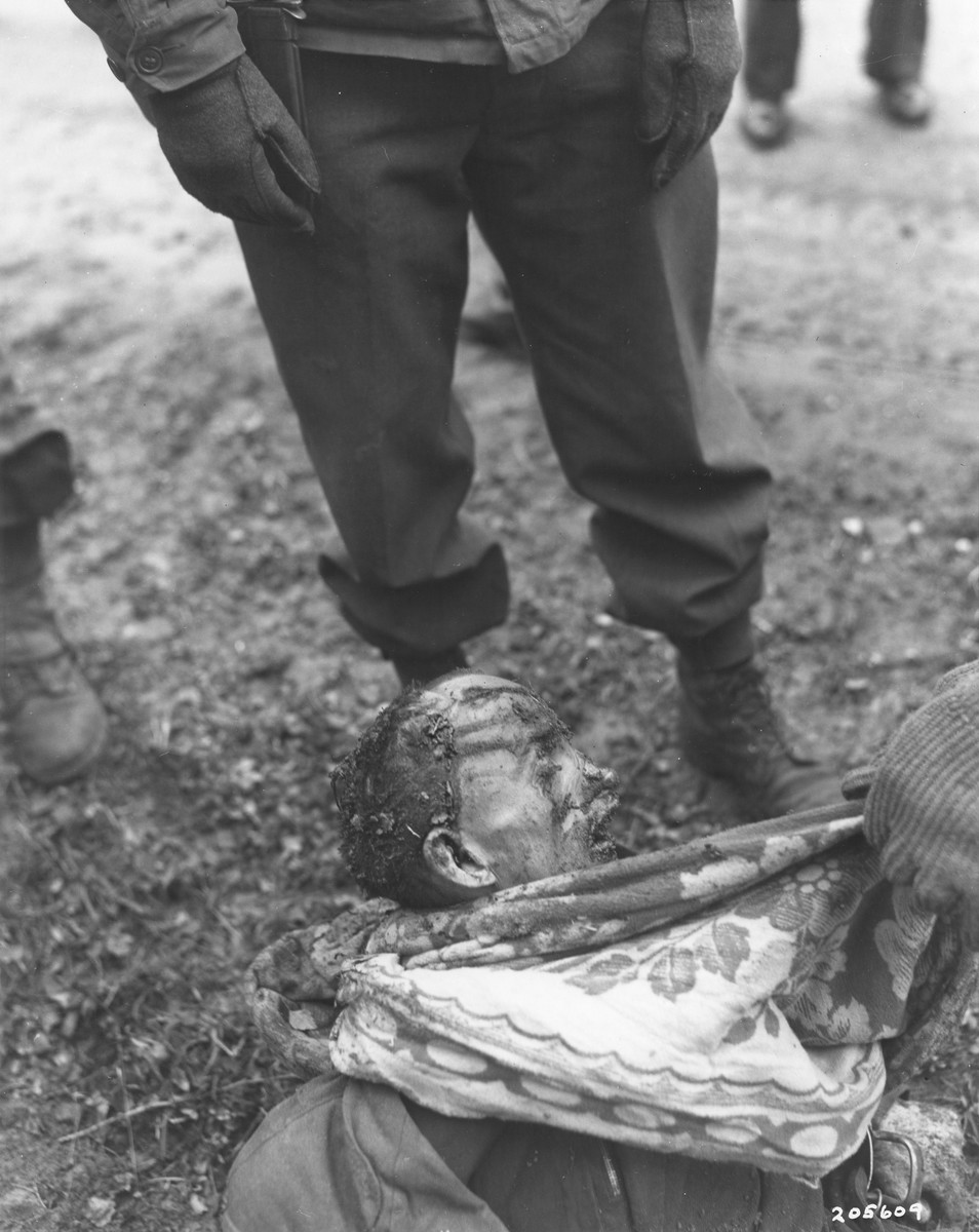 "Members of the 97th Infantry Division, investigating war crimes, examin an exhumed body of a concentration camp prisoners who were killed by the SS while on a death march from Flossenbuerg.  The original caption reads ""This is the body of one of the slave laborers killed during Death March from Flossenburg Concentration Camp near Weiden, Germany.  Many prisoners moved from Flossenburg to another camp as Allies advanced.  Those unable to march were shot and beaten, although suffering from malnutrition, by brutal SS guards.  Some bodies were exhumed during the investigation by Military Government of 97th Division, U.S. third Army.""  By the beginning of April 1945, Allied forces were closing in on the Flossenbuerg concentration camp, which was situated 20 kilometers NE of Weiden, approximately five kilometers from the Czech border.  Several other concentration camps had already evacuated many of their prisoners to Flossenbuerg earlier in the year, including Buchenwald and Auschwitz, so that by the beginning of May the camp and its satellites were overflowing with almost 52,000 prisoners.  Now, because the area was also about to be liberated, a series of evacuation transports was sent southwest by train in the direction of Dachau.  Allied planes already active in the area had successfully destroyed a number of rail lines and locomotives, effectively delaying many of the transports, or forcing them to take alternate routes.  A number of the trains laden with prisoners were even fired on while in transit, accidentally killing prisoners.  Eventually, most of the prisoners were forced to continue their journey on foot because of the destruction to the German rail system.  During these ""death marches,"" numerous prisoners were killed by the SS for lagging behind or stumbling.  When ammunition ran short after several days of marching, the slower and weaker prisoners were beaten to death rather than shot.  Some of the bodies were buried by prisoners who were kept at the back of the group for exactly this purpose.  Others were just left on the side of the road."
