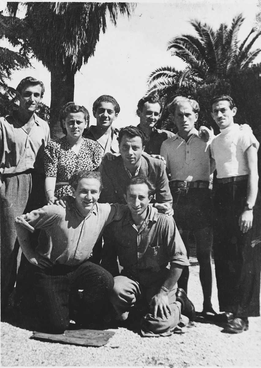 A group of displaced persons poses together in Italy.  Among those pictured are Hela and Szulim Bronner.