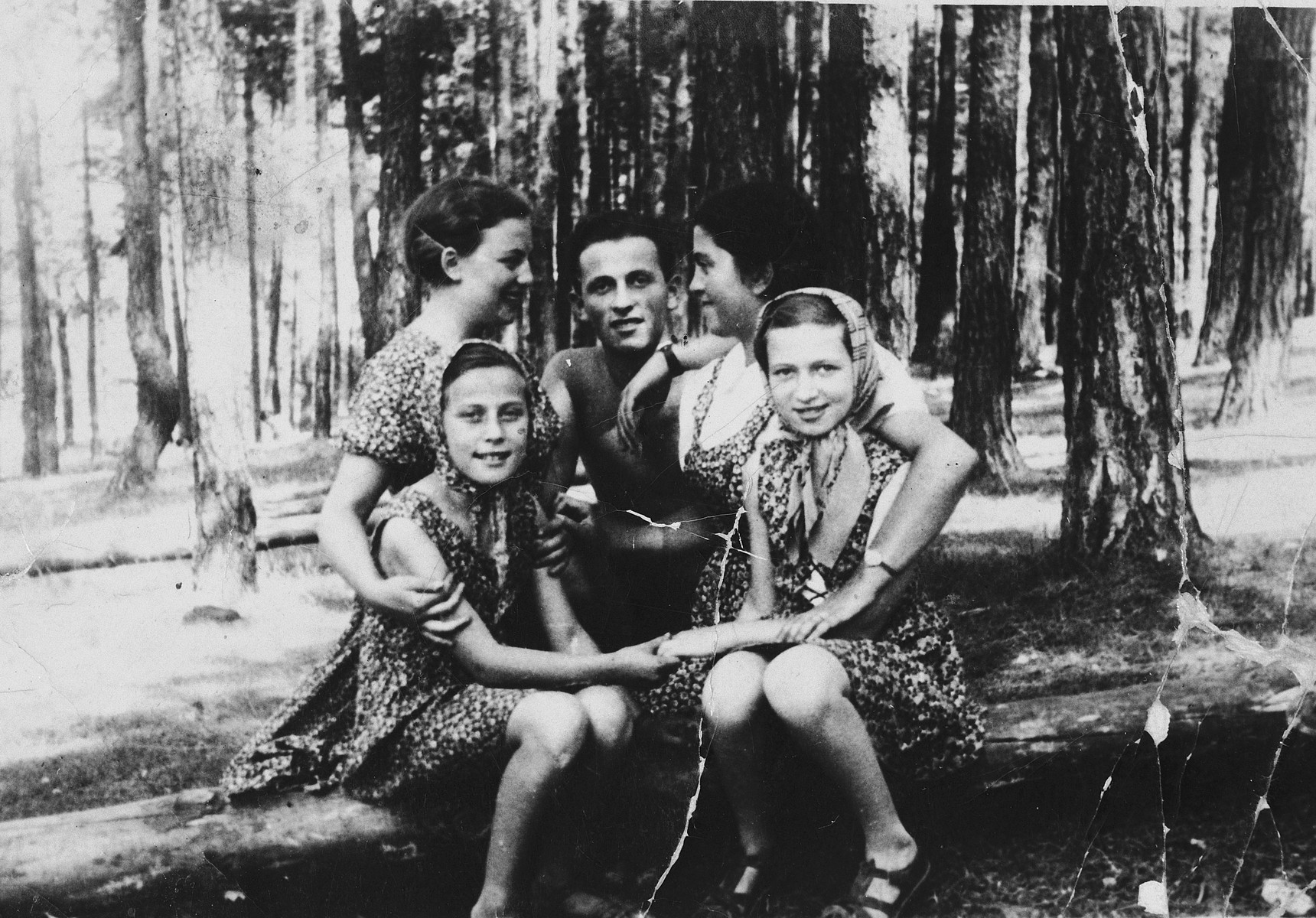 A group of children pose together in a forest near Olkusz.  Seated in front (left to right) are Hela Kolin and Waltman, from Sosnowiec.  Behind them are Rosia (Rachel) Kolin, Schwimmer, and his sister.
