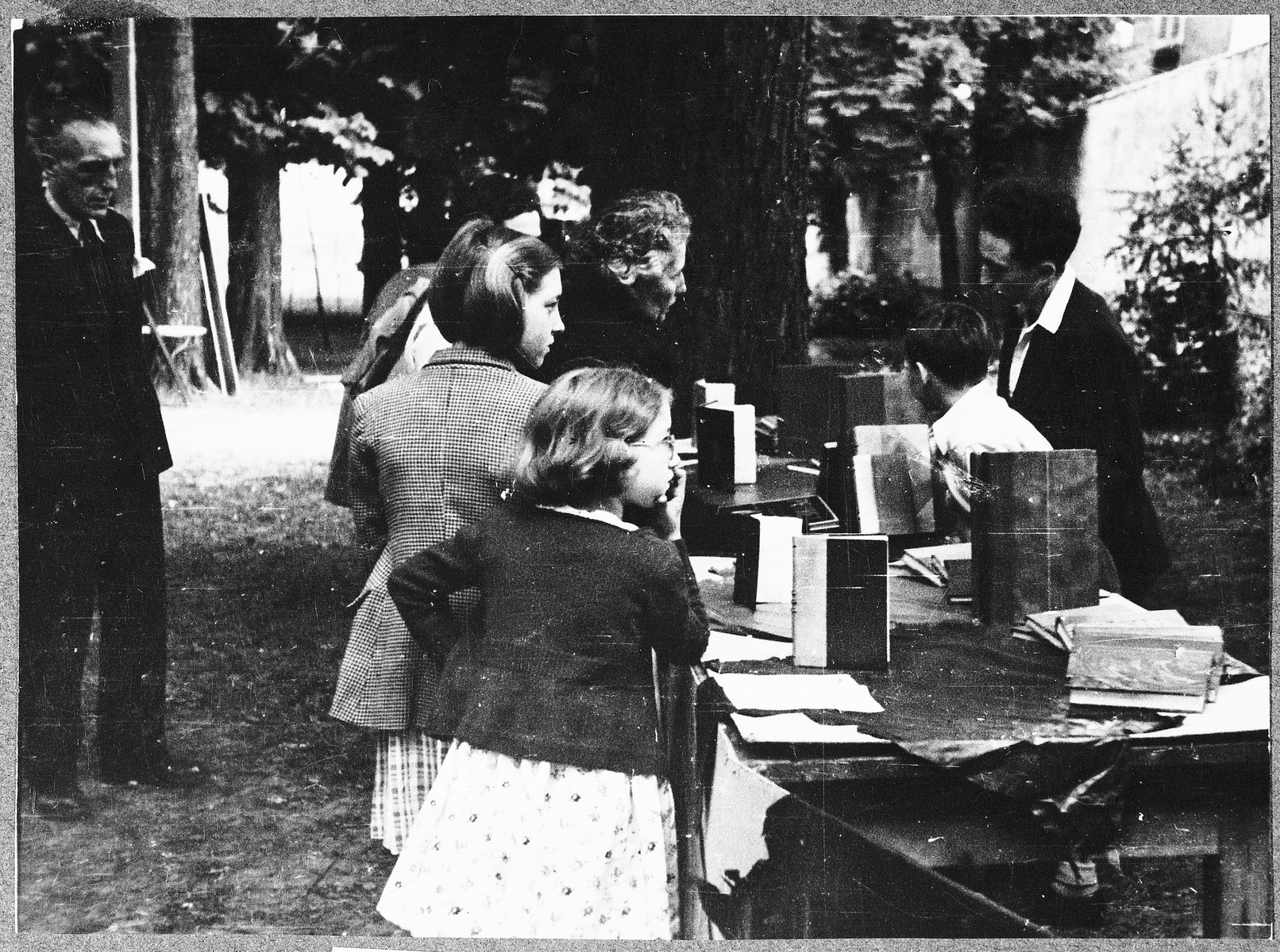 Children look at a display of books created in the Fontenay aux Roses children's home.  Pictured on the right is Erik Goldfarb.