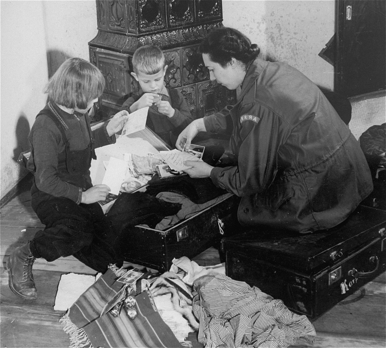 UN relief worker Greta Fischer helps Sophia and Janusz Karpaks pack for a trip to Switzerland, where they will spend several winter months with other  DP children from Prien, under the care of Swiss charitable organizations.