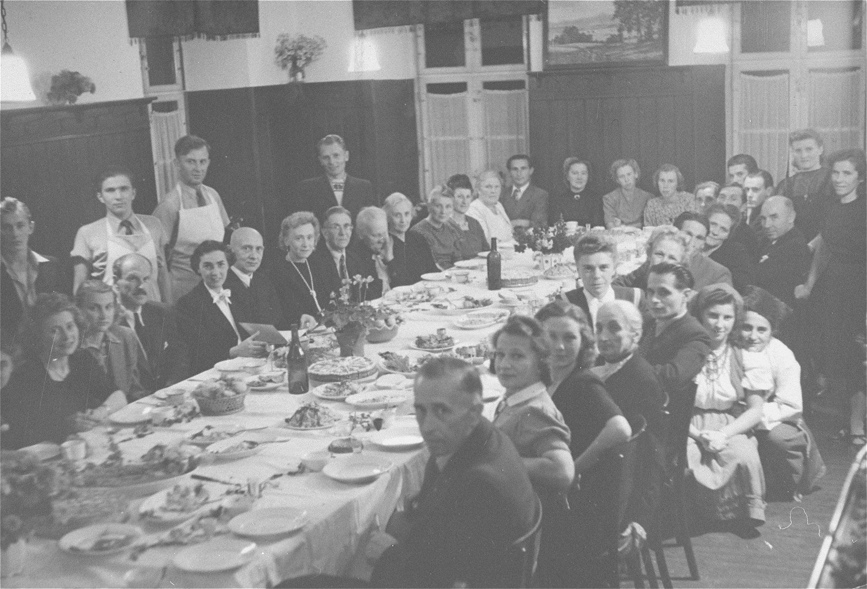 A dinner at the Kloster Indersdorf DP children's center.  UNRRA relief worker, Greta Fischer, is seated fourth from the left.
