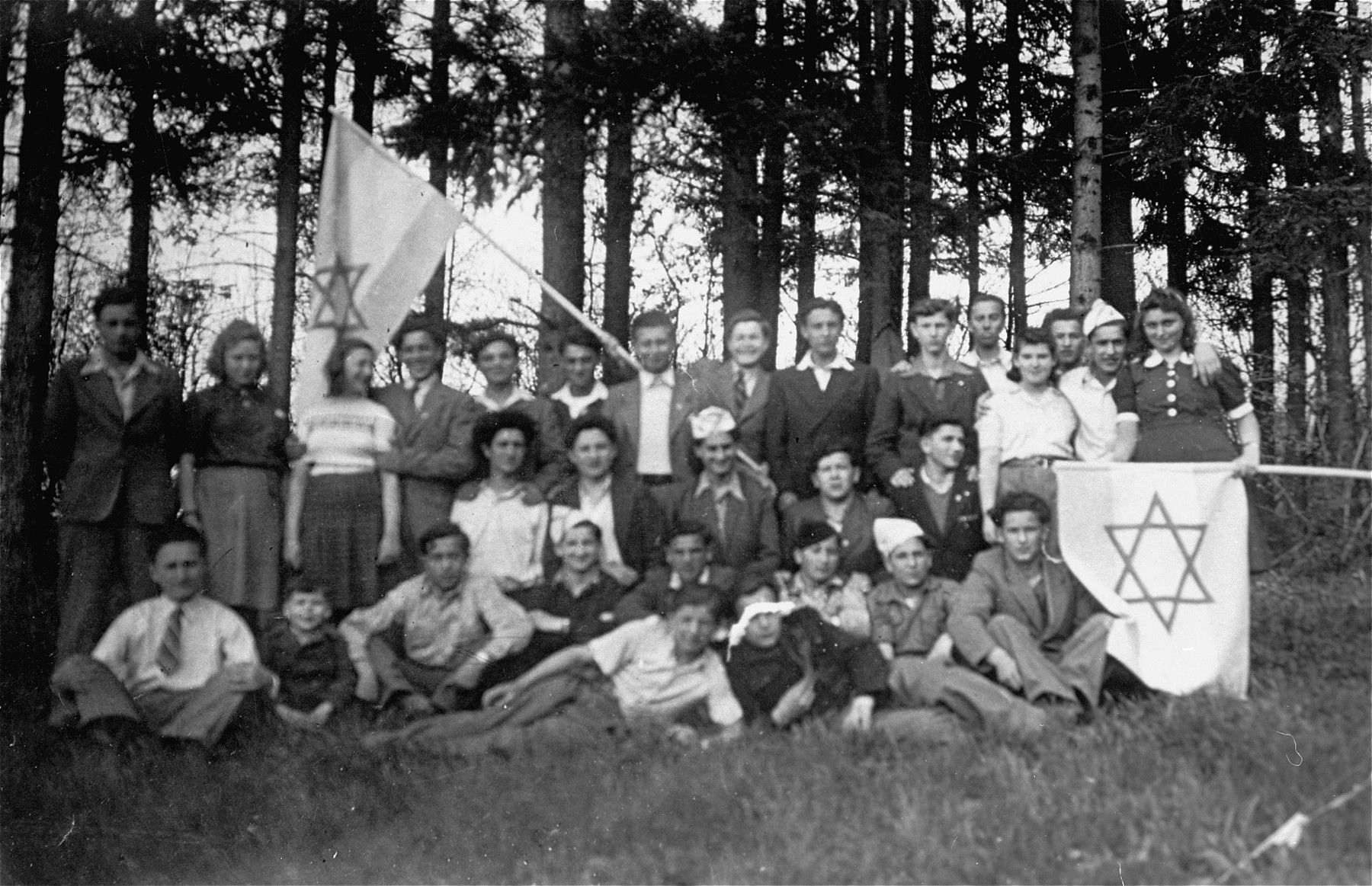 Group portrait of Zionist youth at the Kloster Indersdorf DP children's center.  Among those pictured are Michael Walter (far left), Michael Roth (waving flag, fourth from the left),  Genia Edlerman (in the second to back row, wearing a white blouse) Szlama Weichsblatt (later Sol Wechsler, far left), Nina Krieger, Naftali Steinberg (behind the third person in he front row), Avram Leder, and Nechemia Edlerman (seated, fourth from left wearing a white hat.)
