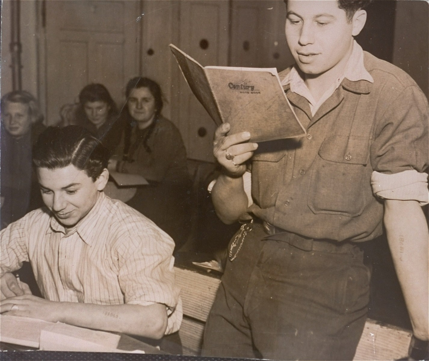 A DP youth reads to his fellow classmates at the Kloster Indersdorf DP children's center.  Standing on the right is Jakob Bulwa, a child survivor of Auschwitz and Flossenbuerg.