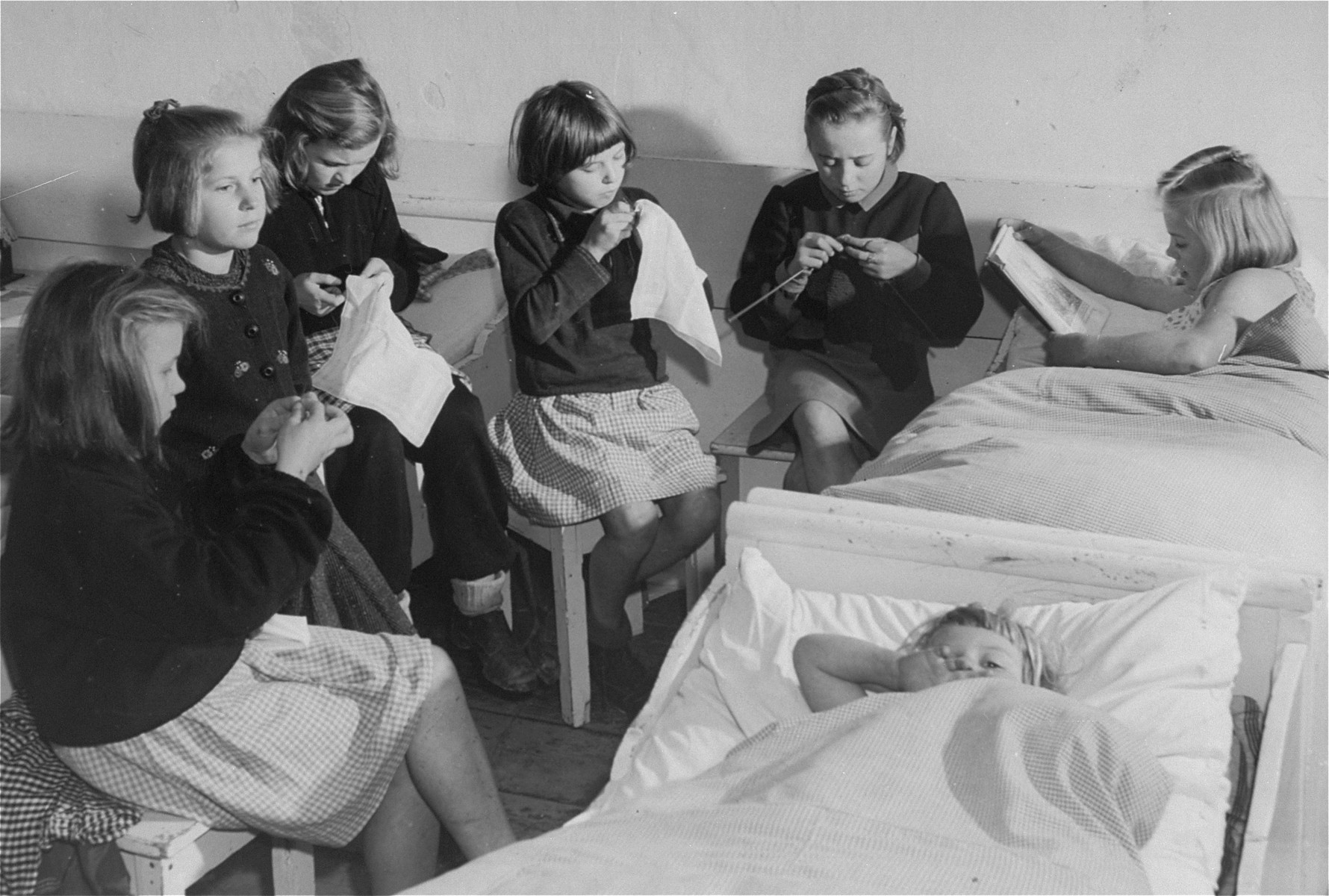 DP girls sew and knit in their living quarters at the Kloster Indersdorf DP children's center.  Pictured in the center is Sofia Karpuk..  Sofia was the daughter of a former forced laborer.  Most of the other girls came from Upper Silesia.  Their German teacher brought her class to Bavaria to escape Soviet troops.