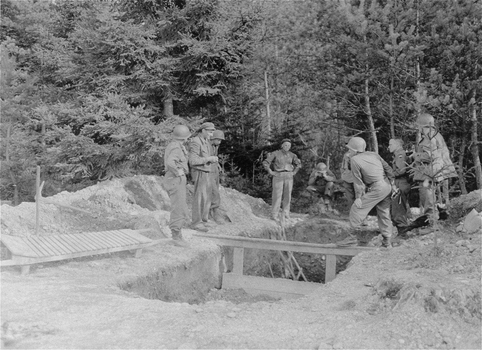 Officers and men of 14th Armoured Division, 3rd U.S. Army, inspect a mass grave in the Ampfing concentration camp alleged to hold 2240 bodies.