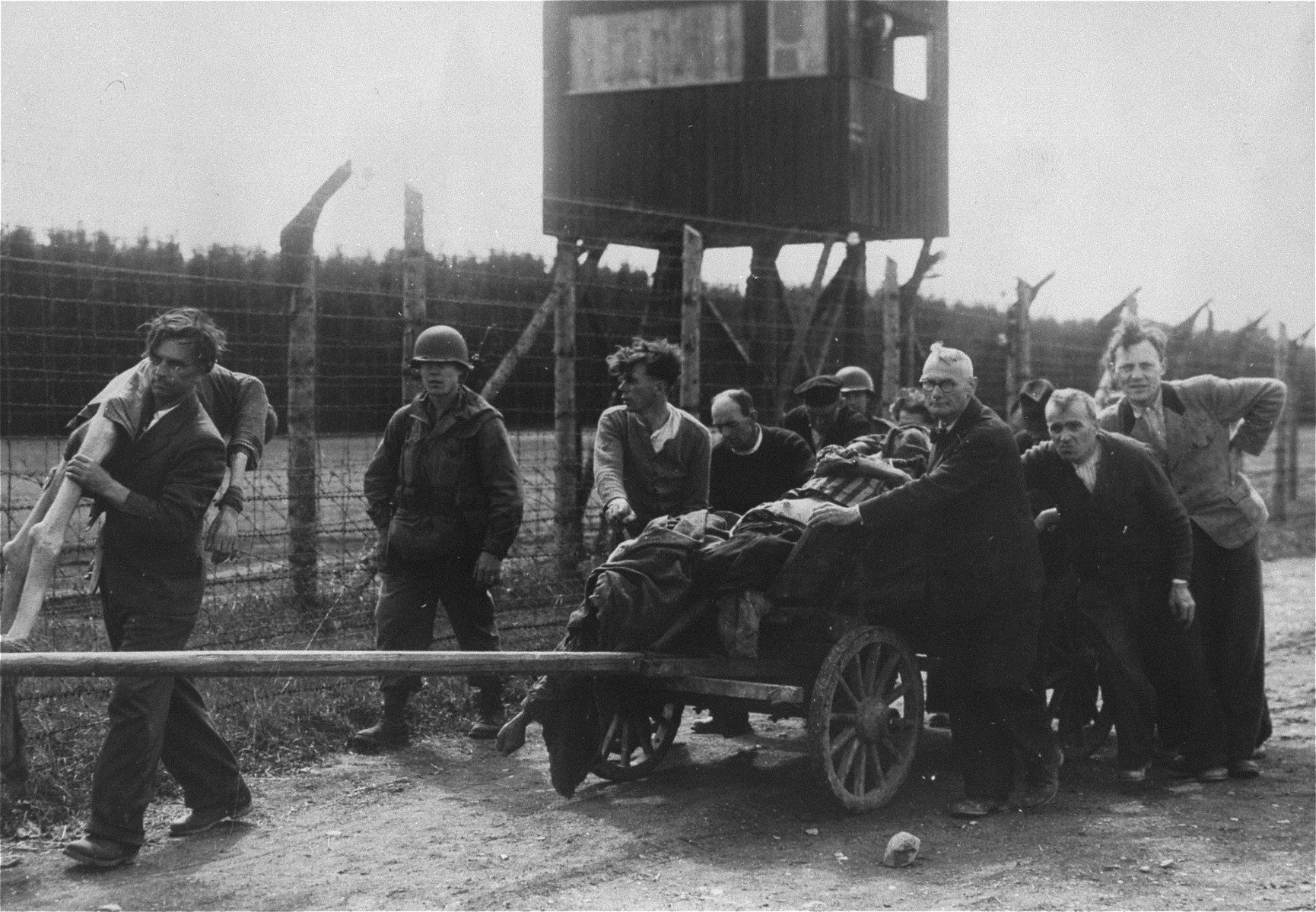 German civilians in Hurlach push a wagon laden with corpses to a mass grave for burial.