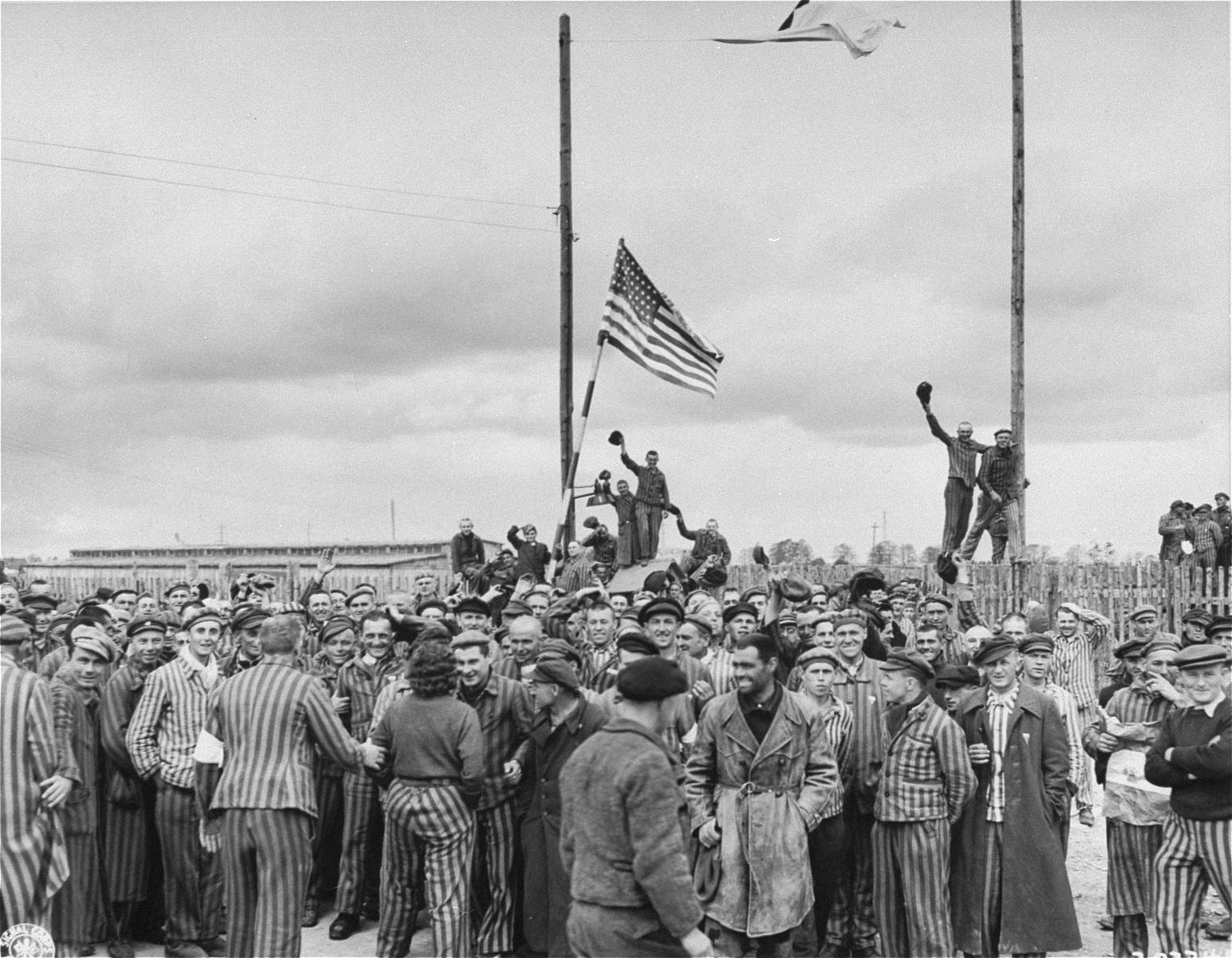 "Inmates waving a home-made American flag greet U.S. Seventh Army troops upon their arrival at the Allach concentration camp.    Three survivors pictured in the photo are: Martin Kaufman (b. in Krashnik, Poland); Leizer Fajerman (b. Sulejow, Poland, standing on right in a full length coat holding a cigarette); and Irving Miesing (Yitzhak Misengiser). The man in the long coat has alternatively been identified as Eli Okon from Bialystock.  Original caption reads, ""After American troops arrived, homemade American flag was raised by the prisoners of Dachau prison camp. As it waved in the breeze, it  seemed to reflect the joy of inmates who realize  freedom for the first time in many years."""