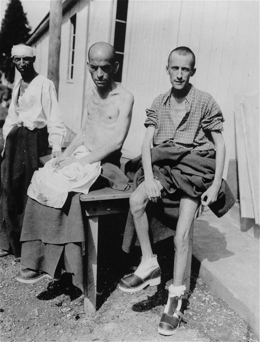 Two Hungarian Jews in Ampfing rest in the sun after the liberation of the camp by the 3rd U.S. army.