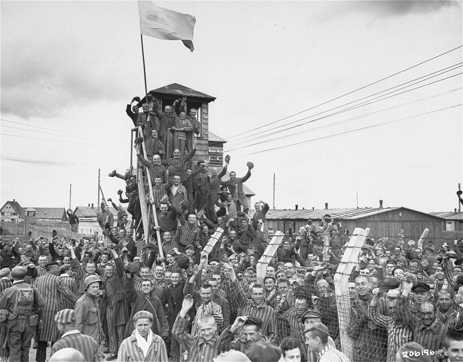 "Survivors in Allach, a sub-camp of Dachau, greet arriving U.S. troops.  Among those pictured is Julius Eisenstein.  Original caption reads, ""Prisoners from Dachau in striped uniforms wave and cheer the Seventh Army liberators as the No. 1 Nazi atrocity concentration camp is freed."""