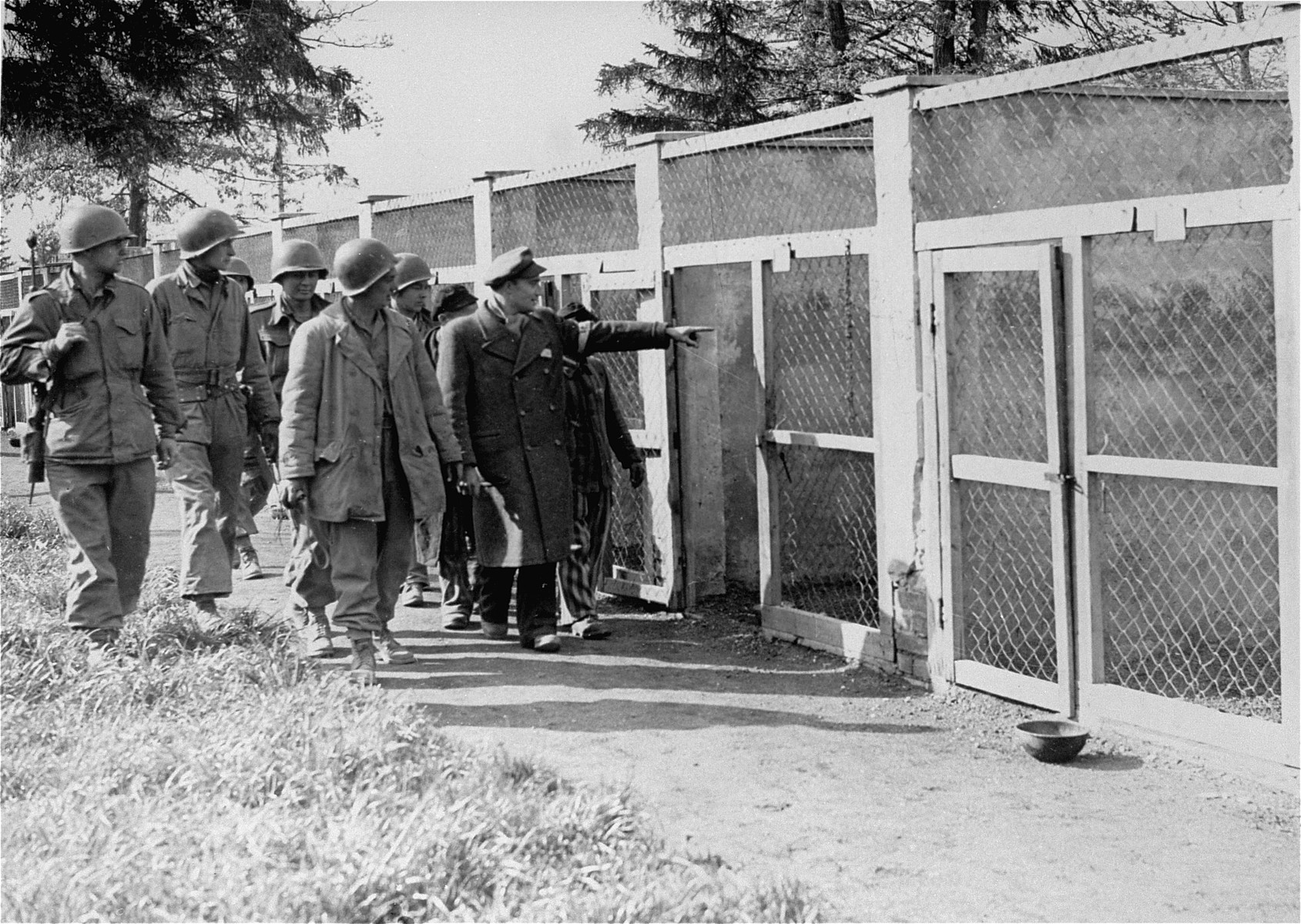 A survivor shows American soldiers the kennels of the SS guard dogs.