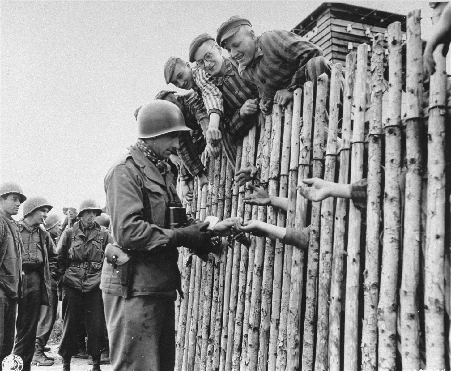 "U.S. Army Corporal Larry Matinsk puts cigarettes into the extended hands of newly liberated prisoners behind a stockade in the Allach concentration camp.  Also pictured are U.S. Army soldiers Arthur Toratti and George Babel (second and third from the left).  Original caption reads, ""Cpl Larry Mutinsk, Philadelphia, PA., hands out his last pack of cigarettes to the eager reaching hands of the prisoners within the wire stockade of the prison camp at Dachau."""