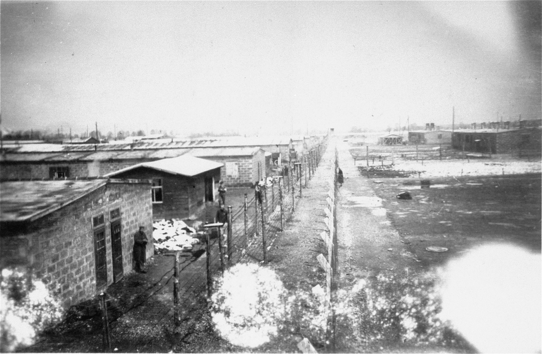 Rear view of the Dachau concentration camp, showing the division between two sectors of the camp and a pile of corpses beside the barracks.