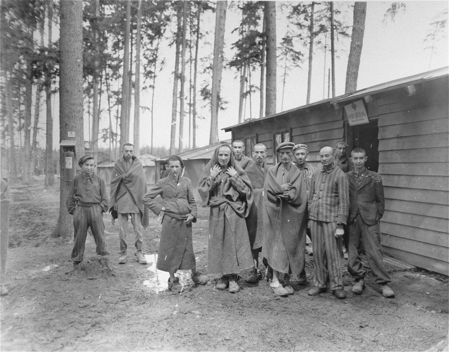 "Survivors in the Ampfing concentration camp stand outside of the ""camp infirmary."""