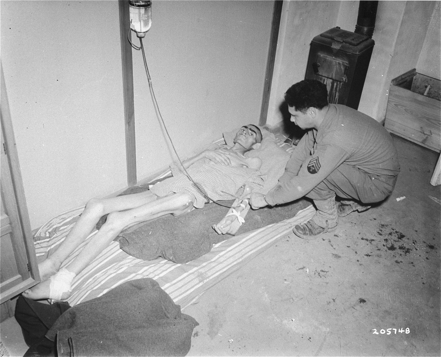 Sargeant Joseph Perlman, of the U.S. Third Army, oversees the intravenous system that feeds this Jewish survivor.