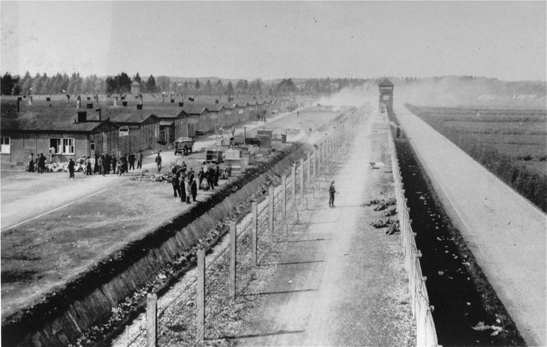 The Dachau concentration camp just after liberation.  An American solider is visible standing in front of the corpses of executed SS guards in the left-center of the photo.