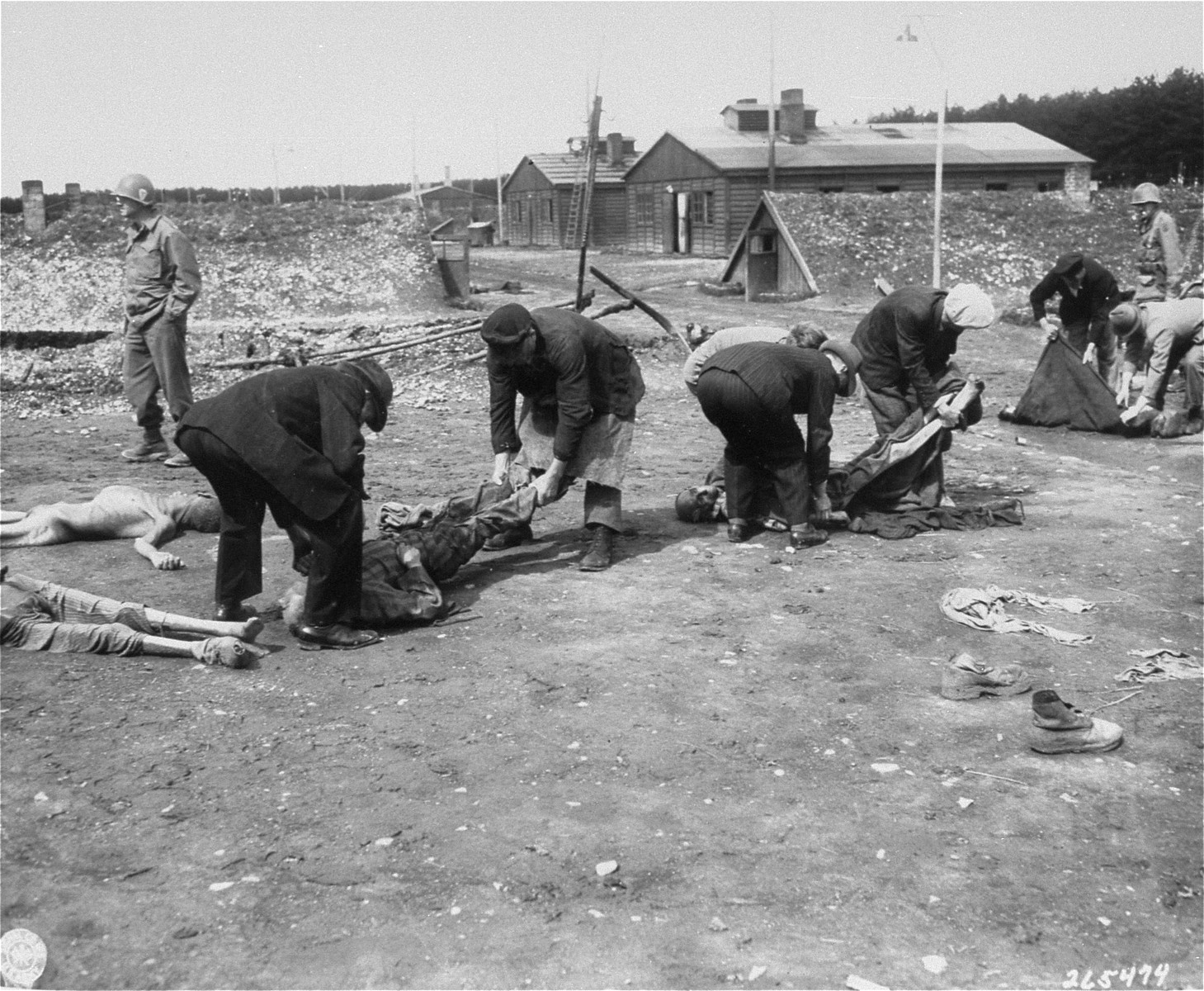 "German civilians from the town of Hurlach move corpses found in Kaufering IV to mass graves for burial.  Original caption reads, ""German Civilians from Landsberg, Germany, are carrying the dead bodies of Russians, Poles, French, and Jewish prisoners,  starved and burned to dead by German S.S. troops at the Stalag #4 concentration camp."""