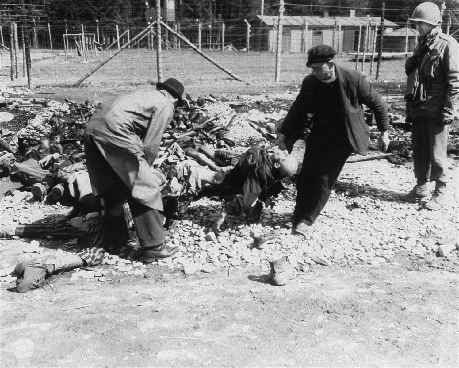 "German civilians from the nearby town of Hurlach move corpses to a mass grave for burial.  Original caption reads, ""German Civilians from the town of Landsberg, are carrying dead political prisoners killed and starved by S.S. Troops, to graves also dug by German civilians at the Stalag #4 concentration camp."""
