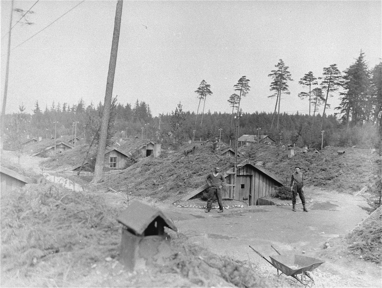 Two survivors stand outside of a barracks in the Ampfing concentration camp.