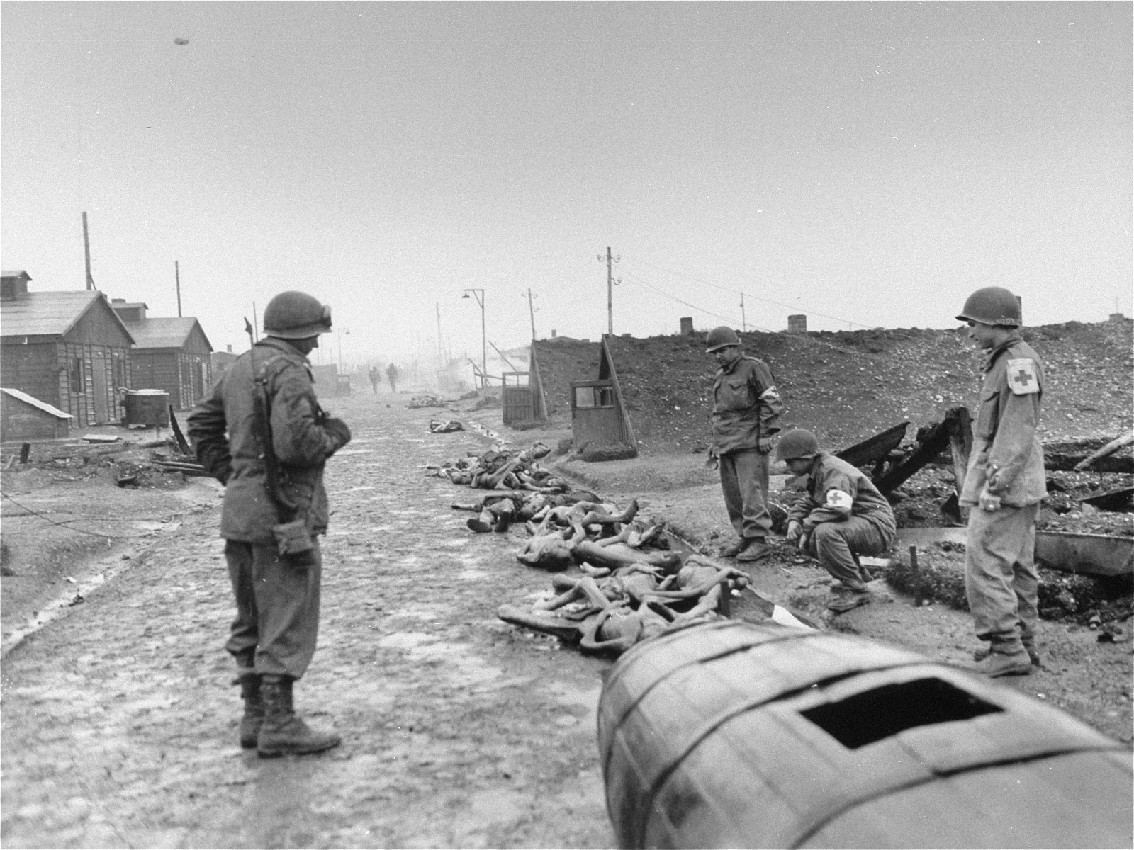 "Troops with the medical detachment of Combat Command A, 12th Armored Division, XXI Corps, U.S. 7th Army, examine the bodies of prisoners killed by the SS just prior to the evacuation of the camp.  Original Caption Reads, ""Landsberg Atrocity: the  emaciated bodies of victims of German cruelty at Landsberg prison. Before retreating in the face of seventh Army attack, the Jewish prisoners were locked in their huts and told they would be shot if they came out. Then the buildings were set on fire. some burned to death in their huts, others found strength  to break down the doors and crawl out to die in the streets. Most prisoners were naked. Some had remnants of clothing on their charred bodies. Here medics examine corpses in front of the ruins of a charred hut."""
