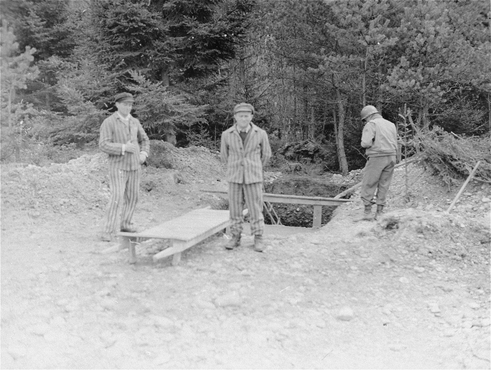 Two survivors and an American soldier stand beside an open mass grave in the Ampfing concentration camp.