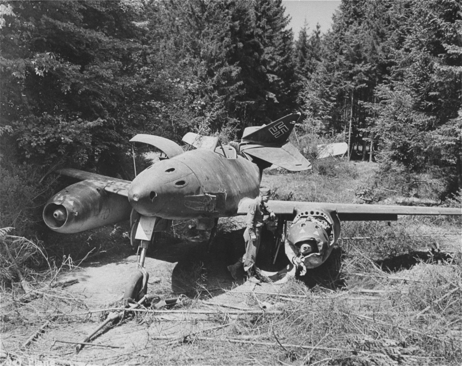 An American soldier investigates a damaged German jet fighter in the vicinity of Dachau.