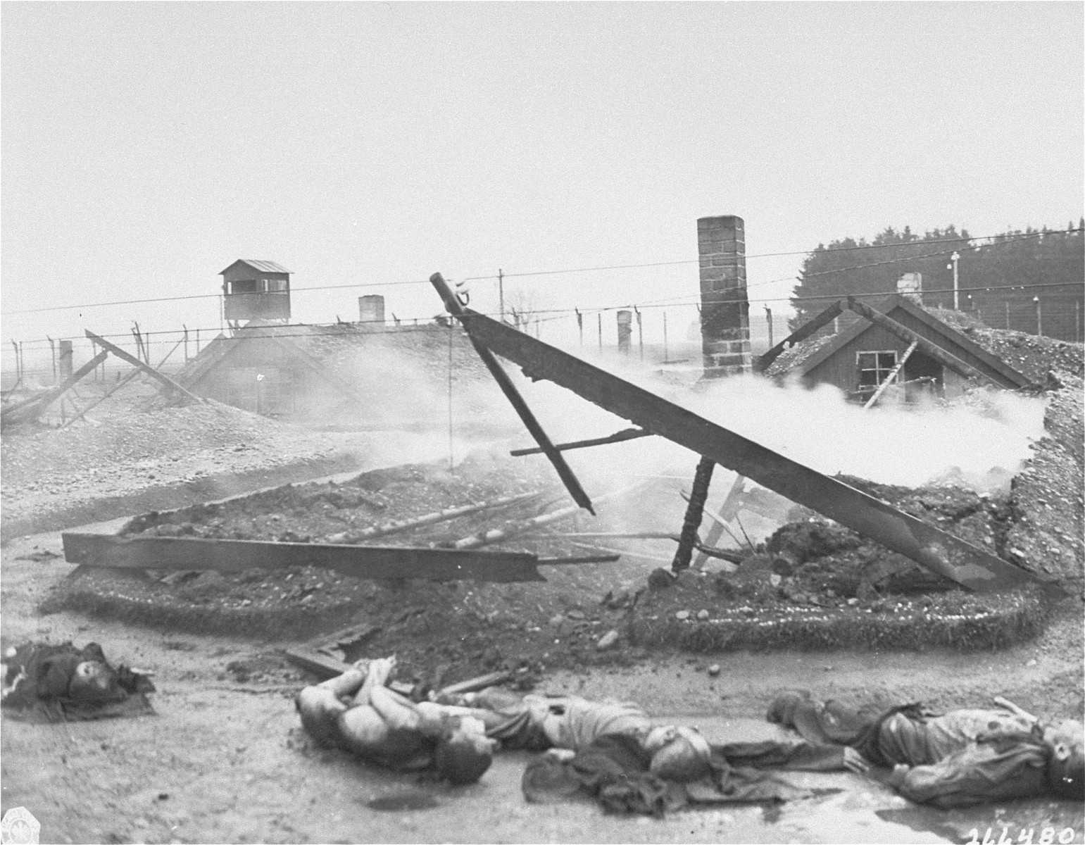 The bodies of slain Jewish slave laborers lie in the street in front of the smoldering ruins of a barracks that was razed by the SS during the evacuation of Hurlach.