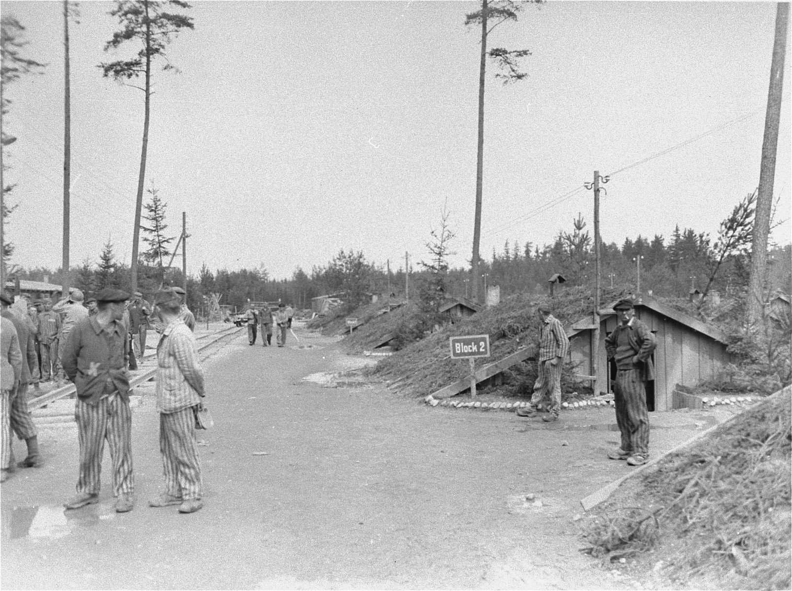 Survivors in the Ampfing concentration camp stand on a camp street outside of their barracks.