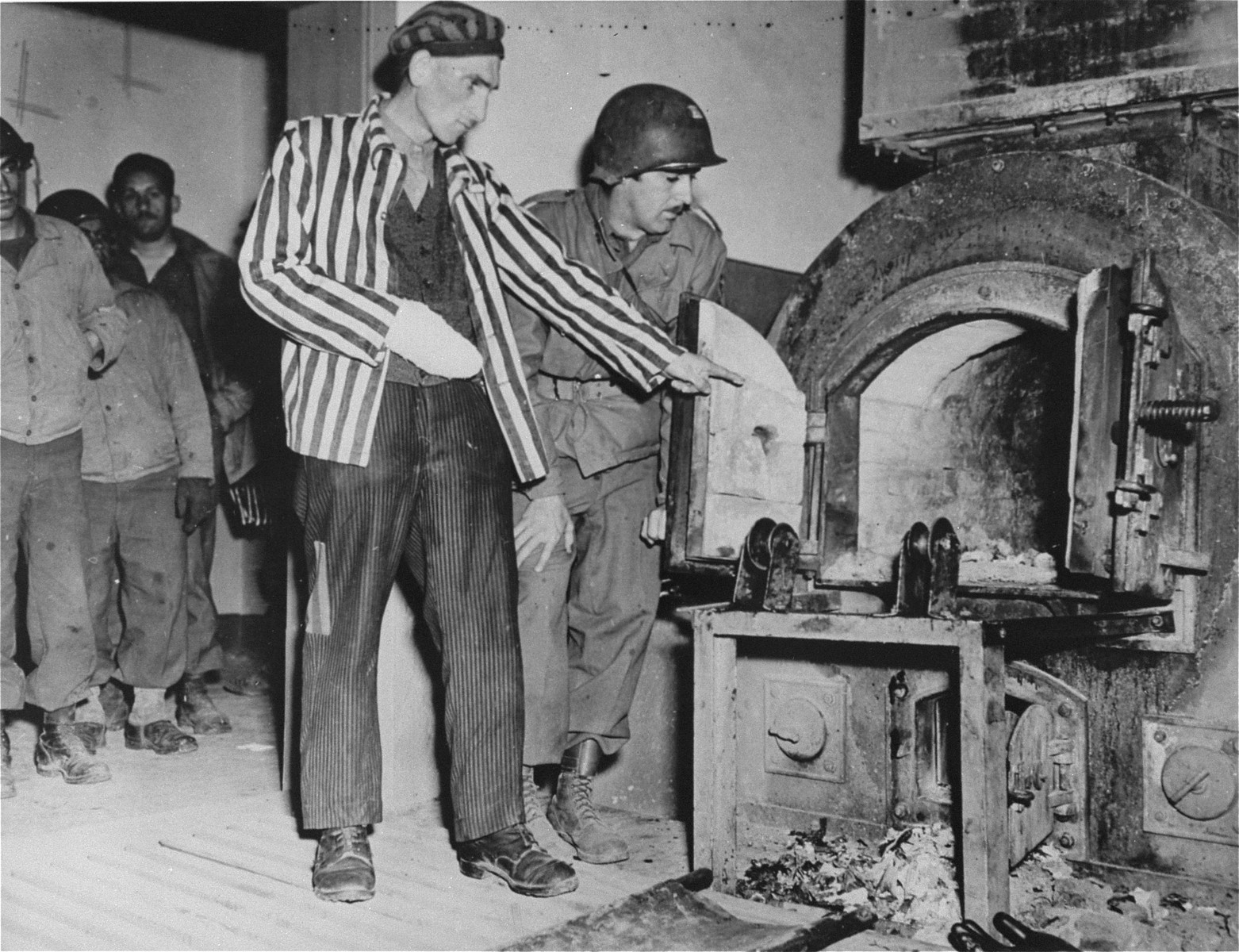 A Polish survivor shows U.S. soldier John L. Lyndon the crematorium ovens used to burn corpses in Dora-Mittelbau.