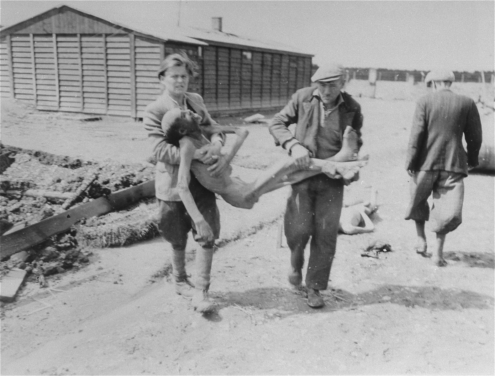 German civilians from the town of Hurlach are forced to carry corpses to mass graves for burial.