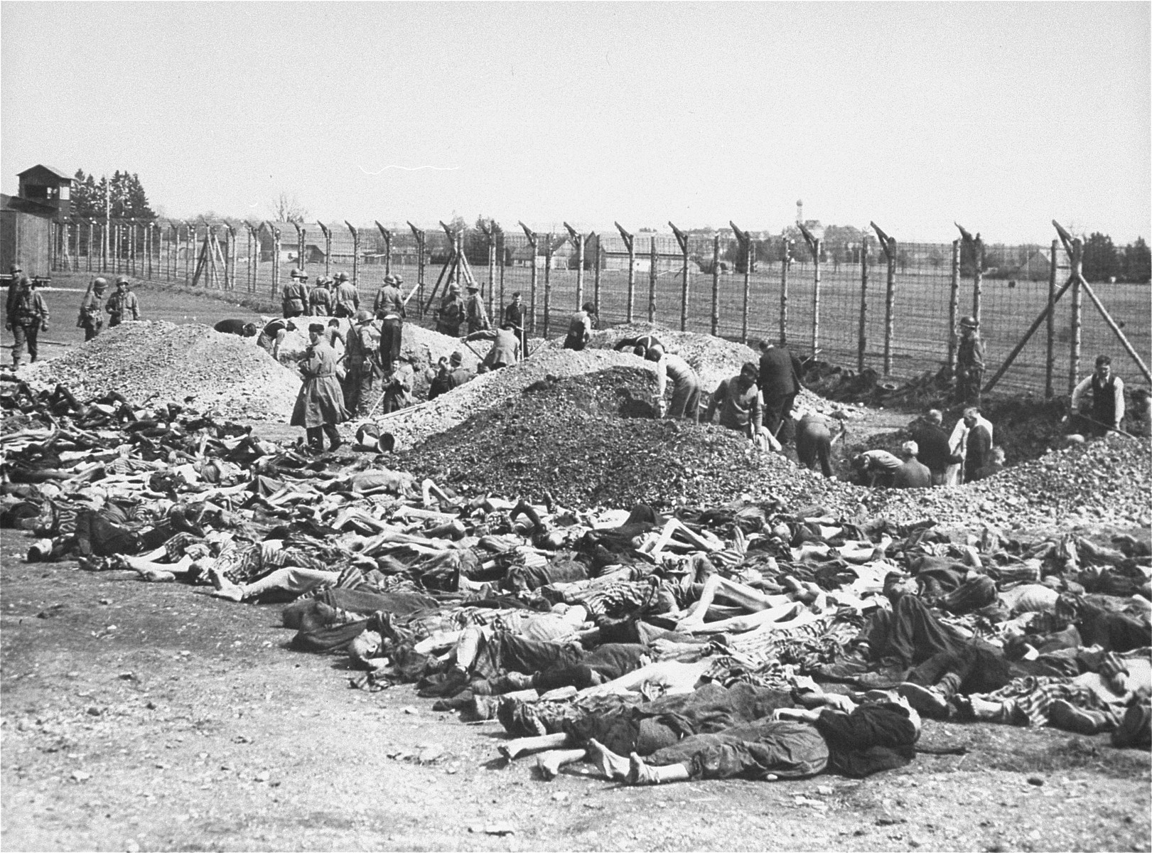 German civilians conscripted by U.S. troops from the surrounding area dig mass graves for the dead found in Kaufering IV.