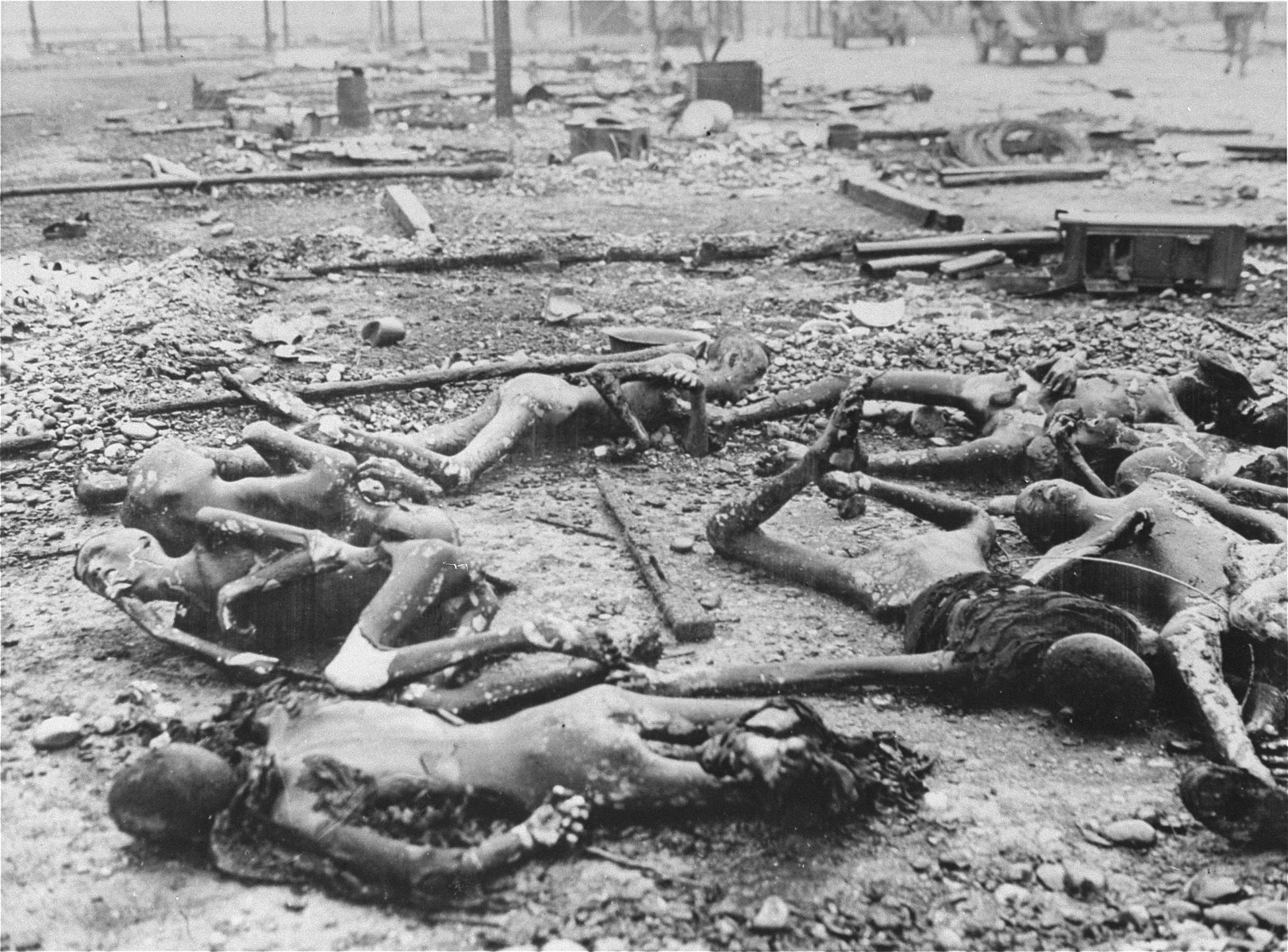 "The charred corpses of prisoners lie amongst trash and rubble in the Kaufering IV concentration camp.  Original caption reads, ""The Landsberg Atrocity: the charred corpses of Jewish prisoners found lying in the ashes of their prison hut set afire by retreating Nazi prison guards at Landsberg. These prisoners were apparently burned alive when they were locked in their wooden huts and told to stay there or be shot by the guards. Burned fragments of clothing cling to some of the emaciated bodies while others are naked."""