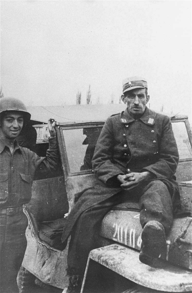 "A captured German guard sits on top of a jeep, while an American soldier Julius Bernstein stands on his right.  The original caption reads, ""German guard I captured hiding in a latrine.   A few minutes after this photo was taken, I was marching the prisoner to an MP truck to be taken away to a POW Interrogation point when one of the 12 survivors sneak-up behind me and the prisoner and sinks a piece of 2x4 in to his head.  He was dead before he hit the ground""."