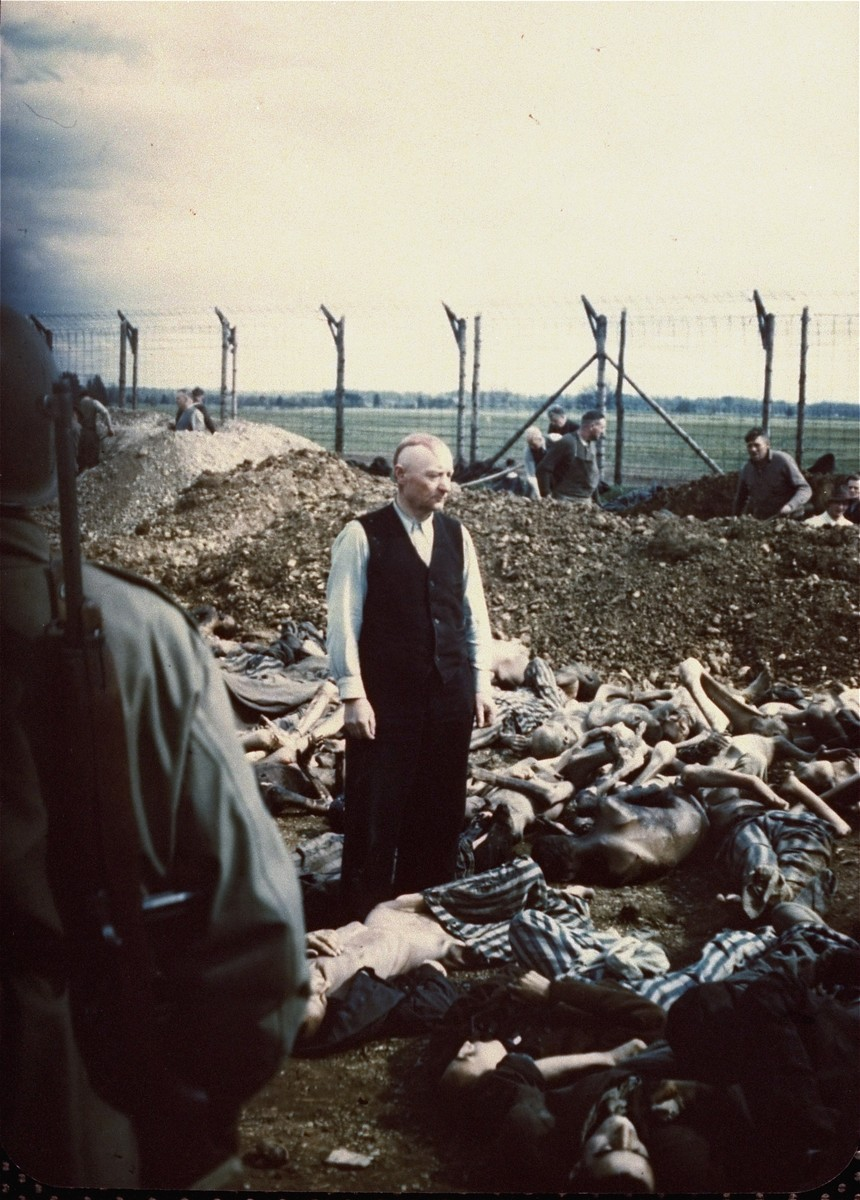 SS officer Eichelsdoerfer, the commandant of Kaufering IV, a sub-camp of Dachau, stands in civilian clothes amidst the corpses of prisoners killed in his camp.  A burial party of Germans conscripted from the surrounding area works in the background.