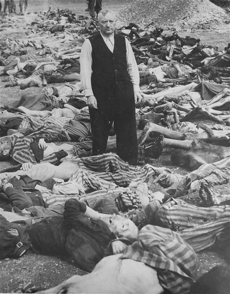 SS officer Johann Baptist Eichelsdoerfer, the commandant of the Kaufering IV concentration camp, stands among the corpses of prisoners killed in his camp.