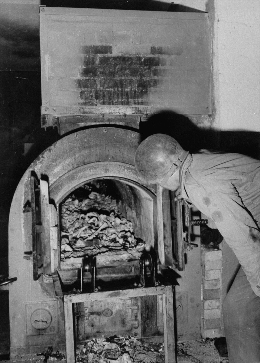 A U.S. soldier looks into a crematorium oven where human remains are visible.