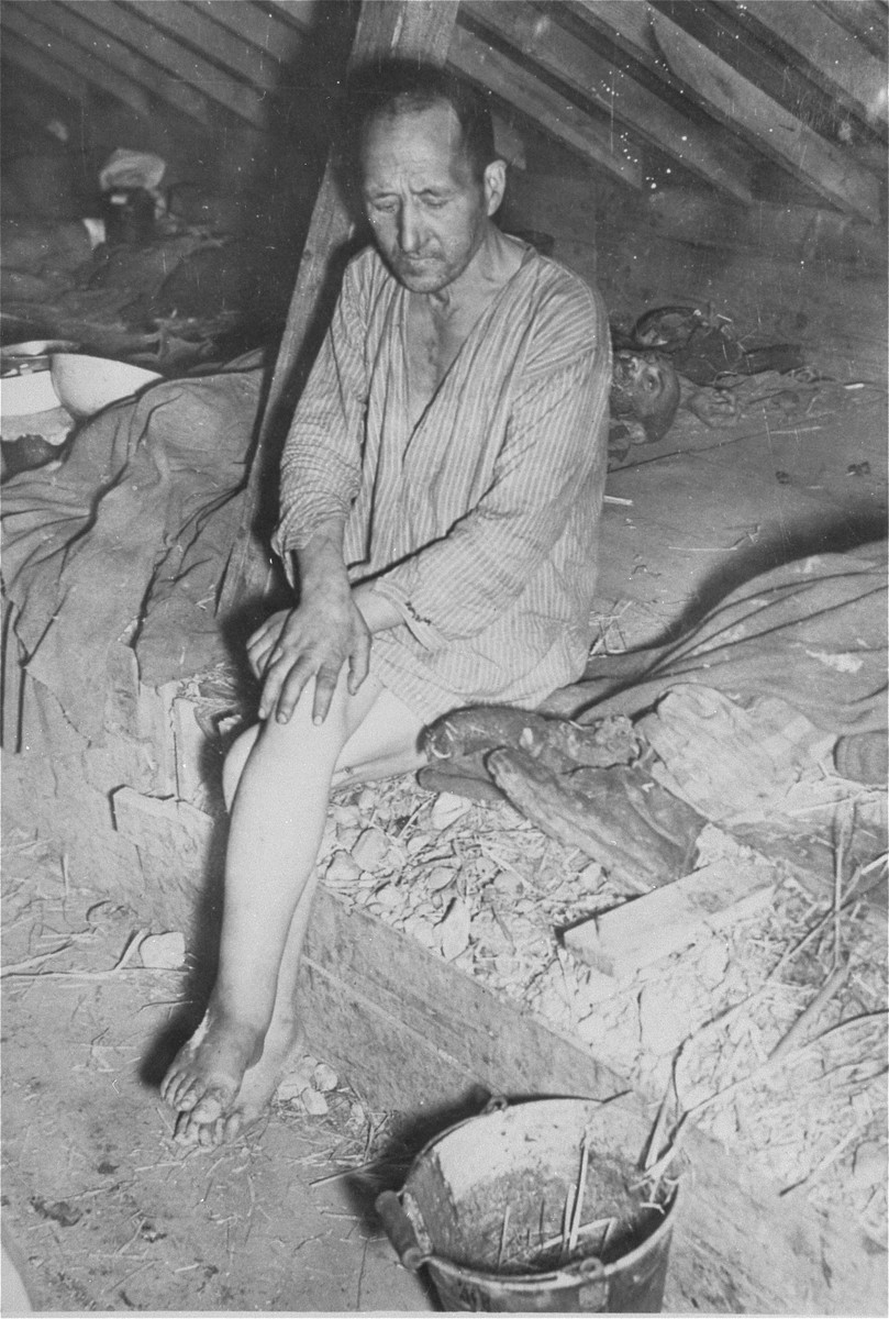 A survivor in the barracks of the Kaufering IV concentration camp.