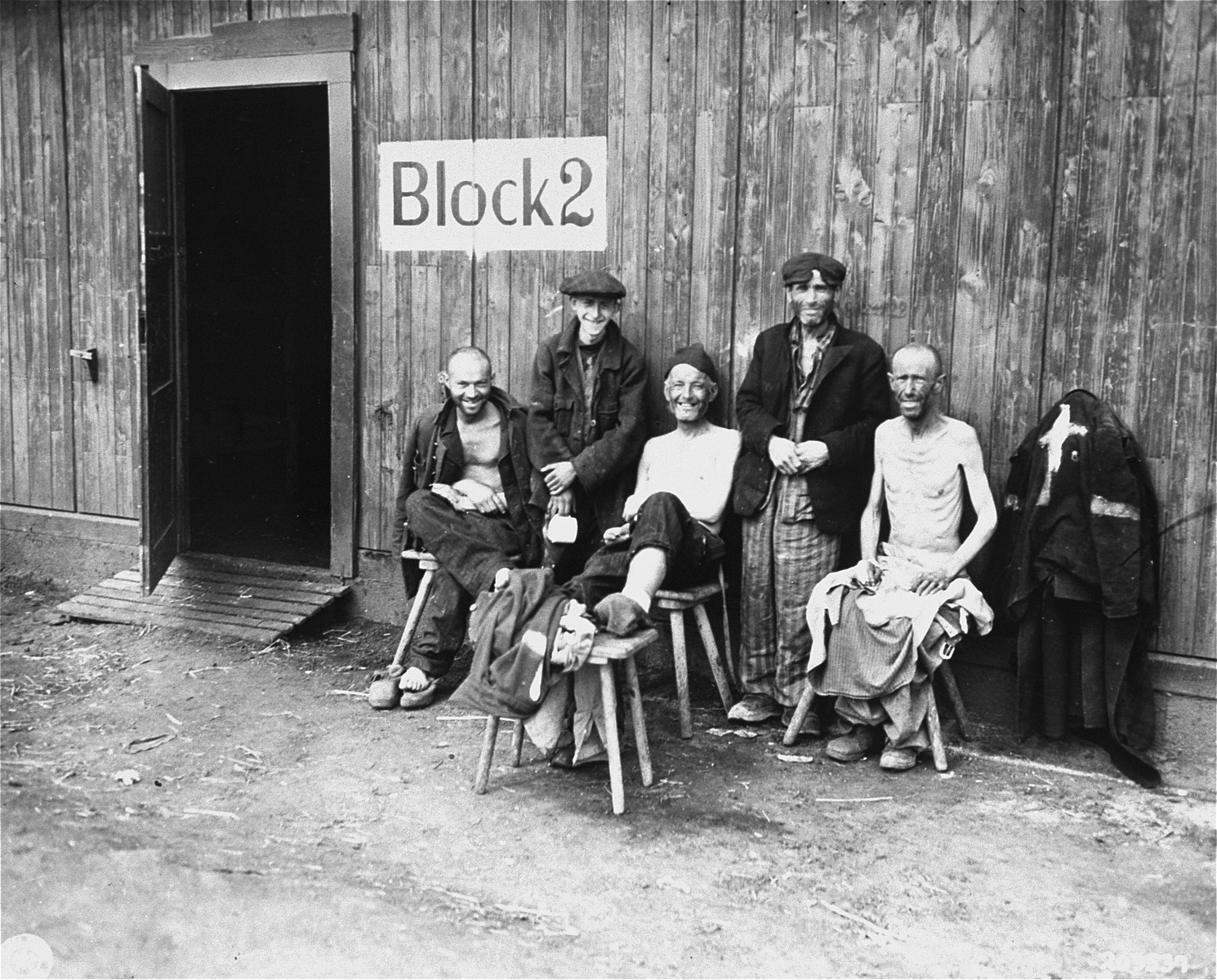 """Five Jewish survivors pose for a U.S. Signal Corps photographer in front of Block 2 in the Hannover-Ahlem concentration camp, a sub-camp of Neuengamme.    The man second from left is Sam Gottesman, now a resident of Pittsburgh, PA in the United States.   The original caption reads """"Liberated, a concentration camp near Hanover, Germany, these five Jews smile happily despite their starved and ill condition.""""  The original Signal Corps caption reads,  """"PNA                                                          EA61998  U.S. TROOPS LIBERATE PRISONERS OF NAZIS Five sick and undernourished Jews are shown before one of the barracks of the Nazi Hanover-Harlen concentration camp near Hanover, Germany, following capture of the city by Ninth U.S. Army troops April 10, 1945.  Hanover is 155 miles west of Berlin.  U.S. Signal Corps Photo ETO-HQ-45-31748. SERVICED BY LONDON OWI TO LIST B-1 CERTIFIED AS PASSED BY SHAEF CENSOR"""