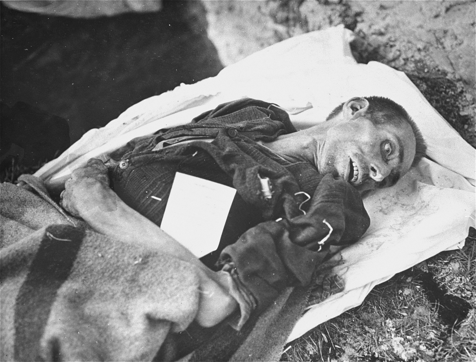 The body of a prisoner who died of starvation.  The tag on his body notes the cause of his death.