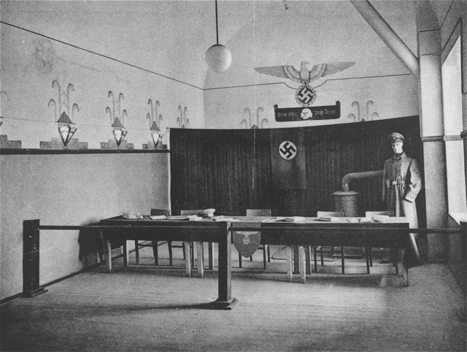 The tribunal room in the fortress prison camp of Breendonck some months after liberation.  It has been decorated with swastikas and other symbols of the Third Reich, as well as with a mannequin wearing an SD uniform.