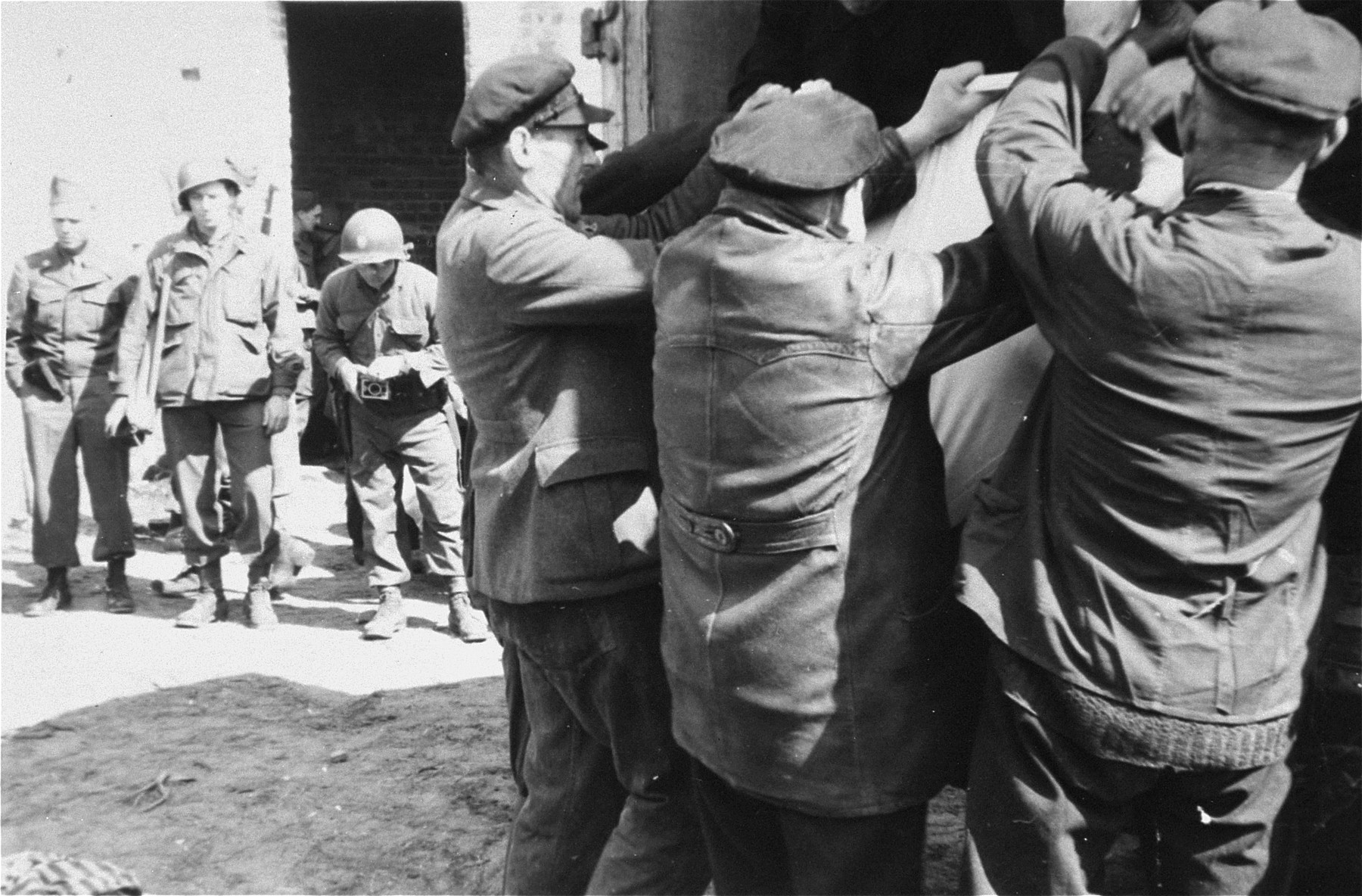 German civilians from the nearby town of Ludwigslust are made to clear corpses from barracks in the Woebbelin concentration camp.