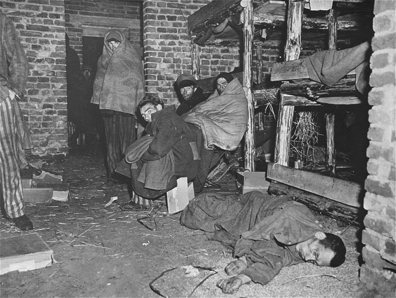 "Survivors wrapped in blankets sit among the dead inside of a barracks in Woebbelin.  The original Signal Corps caption reads, ""NEW NAZI HORROR CAMP DISCOVERED.  One of the worst Nazi concentration camps uncovered by Allied troops was liberated at Wobbelin, Germany, a small town five miles north of Ludwigslust and 90 miles northwest of Berlin.  Soldiers of three Allied units -- the 82nd U.S. Airborne Division, the Eighth Infantry Division of the Ninth U.S. Army and airborne troops of the Second British Army -- entered the camp and found sick, starving inmates barely surviving under indescribable conditions of filth and squalor.  They found hundreds of dead prisoners in one of the buildings while outside, in a yard, hundreds more  were found hastily buried in huge pits.  One mass grave contained 300 emaciated, disfigured corpses.  The dead included Poles, Russians, Frenchmen, Belgians, Dutchmen and Germans, all of whom had been working as slave laborers for the Nazis.  It is estimated that at least 150 of the original 4,000 prisoners succumbed daily, mostly from starvation and savage treatment at the hands of Nazi SS troops who operated the camp.   Some of the bodies found were burned almost beyond recognition and systematic torture of the inmates was revealed by the  physical condition of most of the survivors.  Military Government officers immediately ordered leading citizens of nearby Ludwigslust and other towns to march through the camp and witness the atrocities committed by representatives of the German Government.  Most of the civilians disclaimed any knowledge of the camp's existence despite the fact that many of the prisoners worked in the area.  The local residents later were made to exhume the bodies from the mass graves at the camp and provide decent, respectable interment of all dead prisoners.  Two hundred were buried in the public square of Ludwigslust May 7, 1945, and an equal number were buried in the garden of the highest Nazi official of Hagenow.  Eighty more were laid to rest in the town of Schwerin.  BIPPA                                                           EA 66648  THIS PHOTO SHOWS:  Blanket-wrapped prisoners at the Wobbelin camp huddle near the body of a dead comrade in one of the buildings used as sleeping quarters.  U.S. Signal Corps Photo ETO-HQ-45-45569.  SERVICED BY LONDON OWI (?)LIST B. CERTIFIED AS PASSED BY SHA?F CENSOR."""