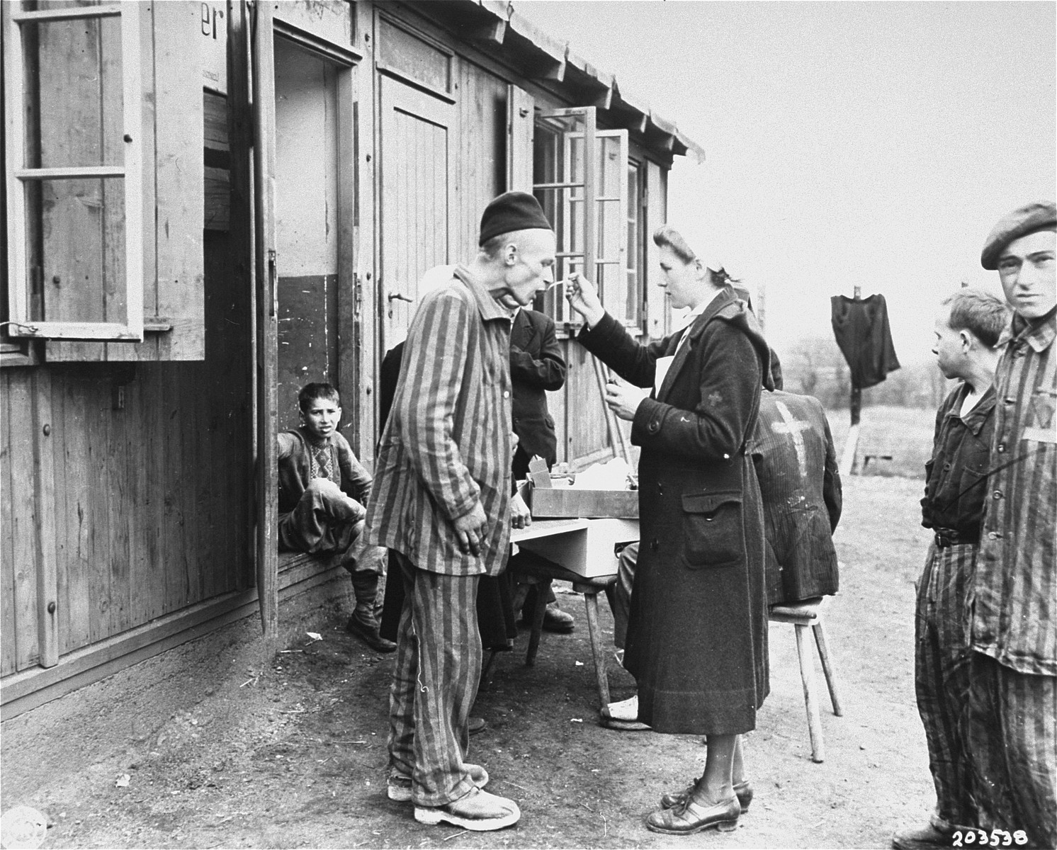 A sick Polish survivor in the Hannover-Ahlem concentration camp receives medicine from a German Red Cross worker.