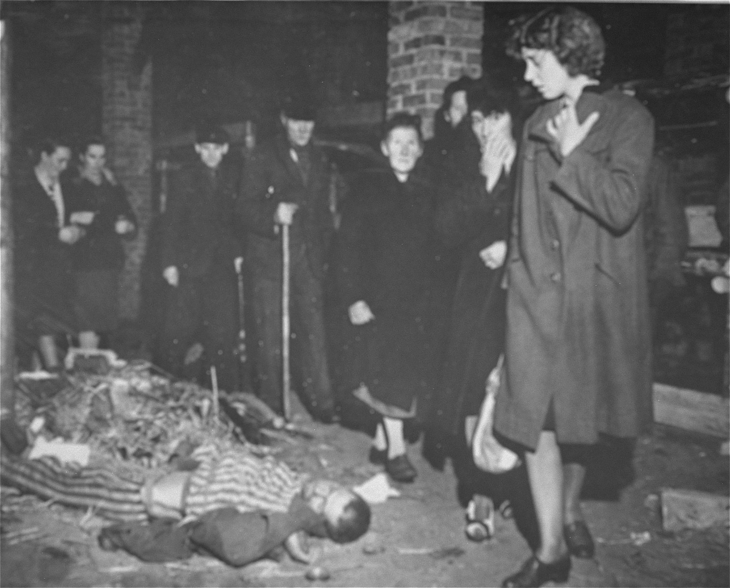 """During a compulsory tour of the Woebbelin concentration camp, German civilians view the bodies of former prisoners in one of the barracks.  The original Signal Corps caption reads, """"NEW NAZI HORROR CAMP DISCOVERED.  One of the worst Nazi concentration camps uncovered by Allied troops was liberated at Wobbelin, Germany, a small town five miles north of Ludwigslust and 90 miles northwest of Berlin.  Soldiers of three Allied units -- the 82nd U.S. Airborne Division, the Eighth Infantry Division of the Ninth U.S. Army and airborne troops of the Second British Army -- entered the camp and found sick, starving inmates barely surviving under indescribable conditions of filth and squalor.  They found hundreds of dead prisoners in one of the buildings while outside, in a yard, hundreds more  were found hastily buried in huge pits.  One mass grave contained 300 emaciated, disfigured corpses.  The dead included Poles, Russians, Frenchmen, Belgians, Dutchmen and Germans, all of whom had been working as slave laborers for the Nazis.  It is estimated that at least 150 of the original 4,000 prisoners succumbed daily, mostly from starvation and savage treatment at the hands of Nazi SS troops who operated the camp.   Some of the bodies found were burned almost beyond recognition and systematic torture of the inmates was revealed by the  physical condition of most of the survivors.  Military Government officers immediately ordered leading citizens of nearby Ludwigslust and other towns to march through the camp and witness the atrocities committed by representatives of the German Government.  Most of the civilians disclaimed any knowledge of the camp's existence despite the fact that many of the prisoners worked in the area.  The local residents later were made to exhume the bodies from the mass graves at the camp and provide decent, respectable interment of all dead prisoners.  Two hundred were buried in the public square of Ludwigslust May 7, 1945, and an equal number were buried in"""