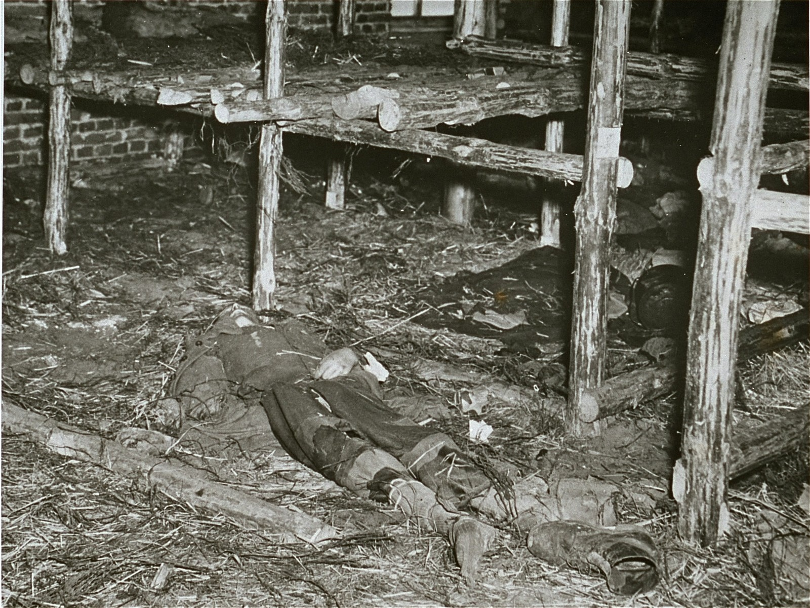 """The body of a former prisoner lies on the ground of a barracks of the Woebbelin concentration camp.  Original Caption: """"This camp, recently captured by troops of the US Ninth Army, had prisoners who starved to death. Here one lies on the floor in the living quarters of the prisoners."""""""