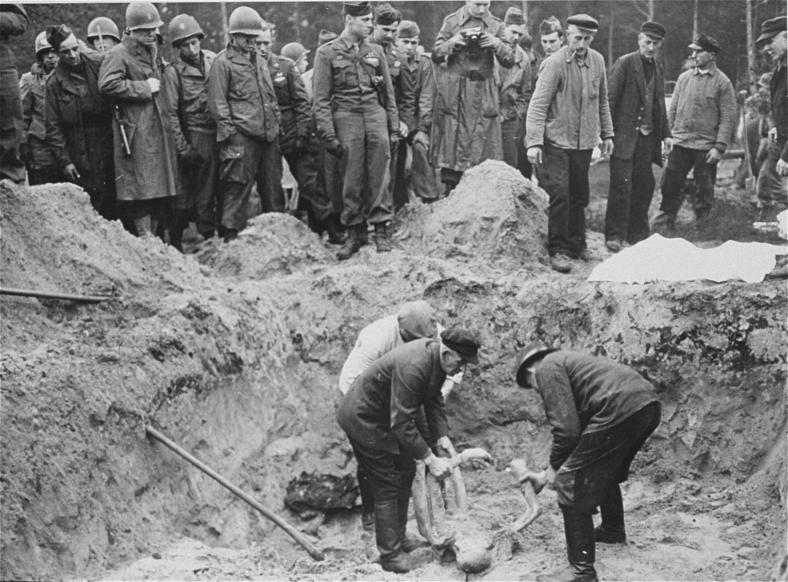 "American troops with the 82nd Airborne Division look on as German exhume corpses from a mass grave.   The original Signal Corps caption ""NEW NAZI HORROR CAMP DISCOVERED.  One of the worst Nazi concentration camps uncovered by Allied troops was liberated at Wobbelin, Germany, a small town five miles north of Ludwigslust and 90 miles northwest of Berlin.  Soldiers of three Allied units -- the 82nd U.S. Airborne Division, the Eighth Infantry Division of the Ninth U.S. Army and airborne troops of the Second British Army -- entered the camp and found sick, starving inmates barely surviving under indescribable conditions of filth and squalor.  They found hundreds of dead prisoners in one of the buildings while outside, in a yard, hundreds more  were found hastily buried in huge pits.  One mass grave contained 300 emaciated, disfigured corpses.  The dead included Poles, Russians, Frenchmen, Belgians, Dutchmen and Germans, all of whom had been working as slave laborers for the Nazis.  It is estimated that at least 150 of the original 4,000 prisoners succumbed daily, mostly from starvation and savage treatment at the hands of Nazi SS troops who operated the camp.   Some of the bodies found were burned almost beyond recognition and systematic torture of the inmates was revealed by the  physical condition of most of the survivors.  Military Government officers immediately ordered leading citizens of nearby Ludwigslust and other towns to march through the camp and witness the atrocities committed by representatives of the German Government.  Most of the civilians disclaimed any knowledge of the camp's existence despite the fact that many of the prisoners worked in the area.  The local residents later were made to exhume the bodies from the mass graves at the camp and provide decent, respectable interment of all dead prisoners.  Two hundred were buried in the public square of Ludwigslust May 7, 1945, and an equal number were buried in the garden of the highest Nazi official of Hagenow.  Eighty more were laid to rest in the town of Schwerin.  BIPPA                                                          EA 66636  THIS PHOTO SHOWS:  German civilians of Ludwigslust and nearby communities are forced to exhume the bodies of the Nazi atrocity victims from a mass ... Wobbelin concentration camp.  These ... reburied the victims in the town ... gslust.  Troops of the 82nd U.S. ... witness and direct the proceedings ... Photo ETO-..."""