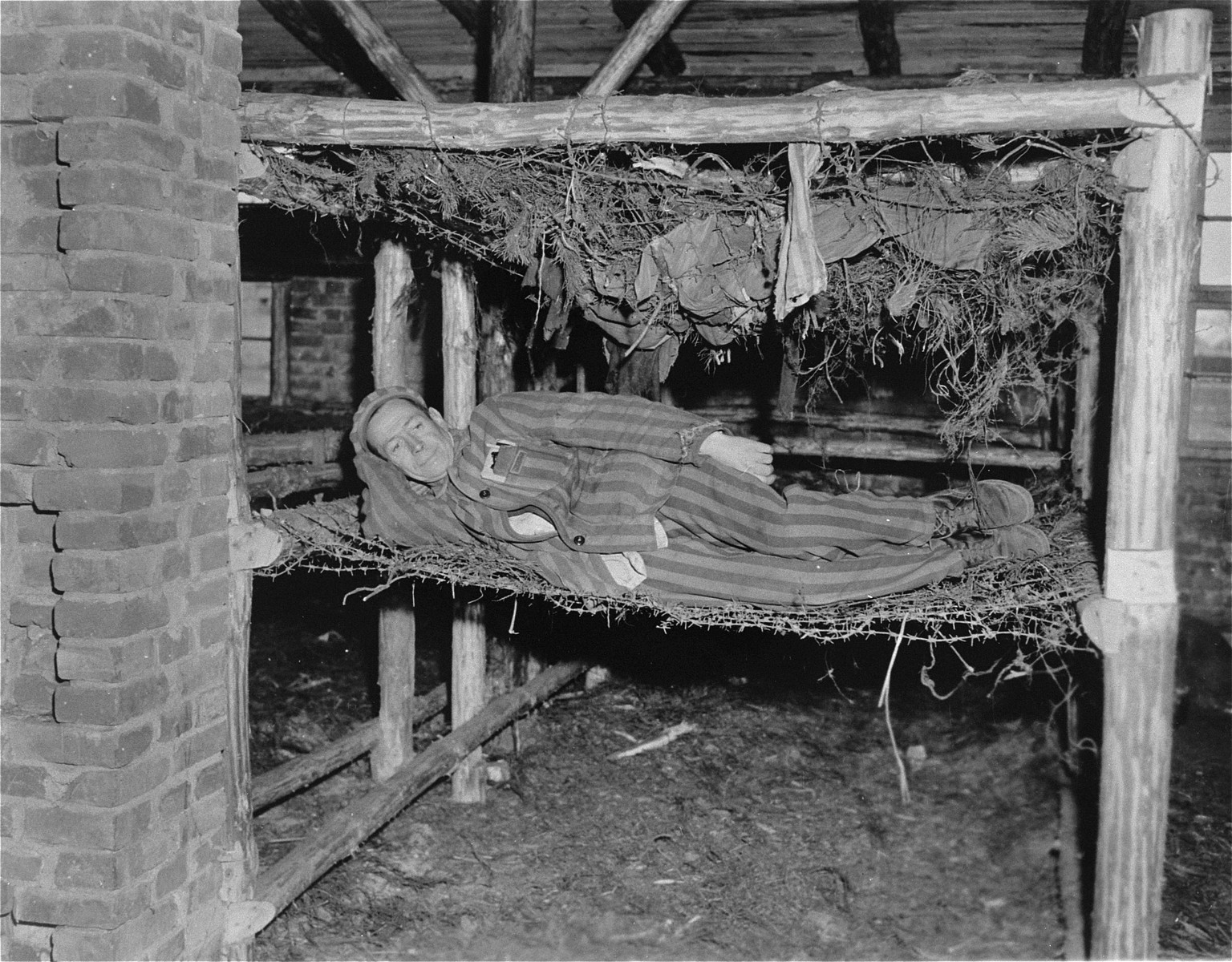 Monsieur Della Giacomo of Limoges, France lies on a bunk made of barbed-wire and rags in the newly liberated Woebbelin concentration camp.
