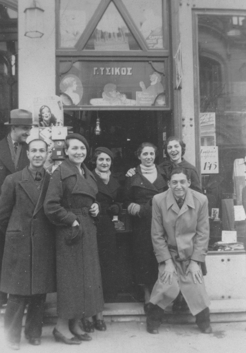 A group of young Greek Jews poses in front of a tobacco store in Salonika.  Among those pictured are Yehuda and Miriam Beraha (front row, left).