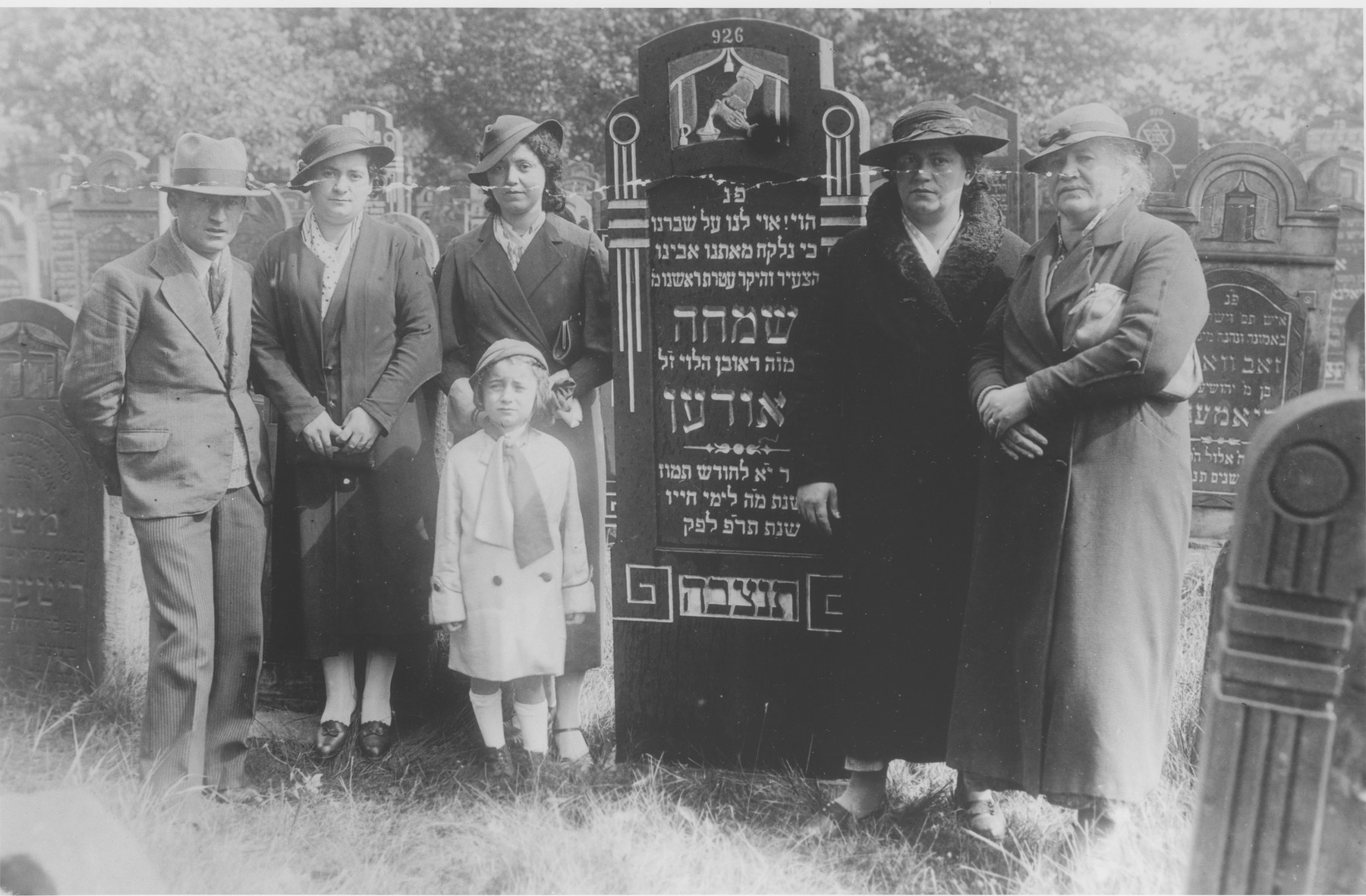 The Laudon family poses next to the tombstone of Symcha Laudon during the unveiling ceremony.  Standing from left to right are Wolf Laudon, Rywka Perla (last name unknown), Cyla Laudon, Maria Frajda's sister and Maria Frajda Laudon.